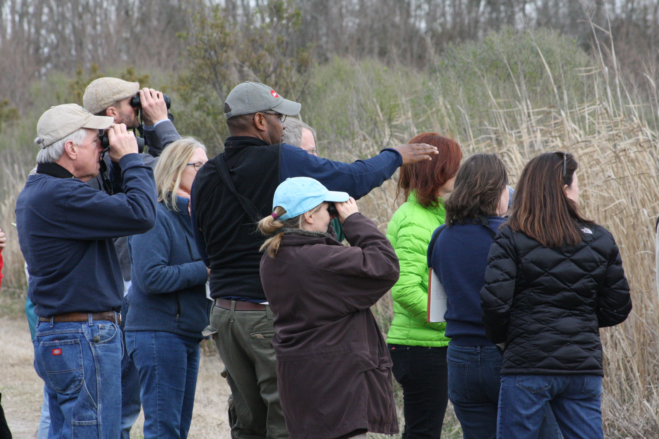 A bird watching class gathered in a group bird watching outdoors alongside their trainer.