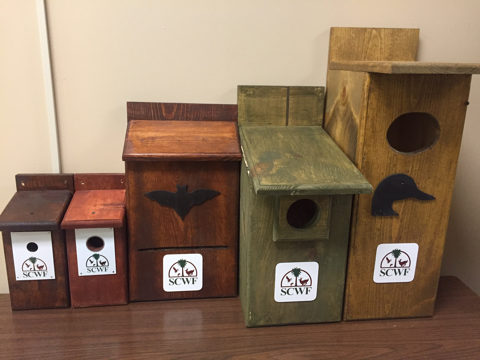 Different types of nesting boxes in red, brown, green, and yellow.