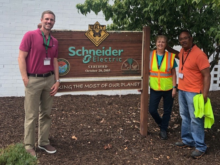 [Image Description] SCWF's Jay Keck (left) with Schneider Electric team members in front of their W.A.I.T. sign.