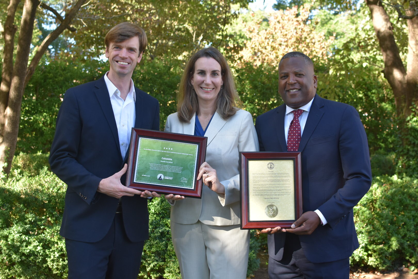 "National Wildlife Federation President and CEO Collin O'Mara, South Carolina Wildlife Federation's Sara Green and City of Columbia Mayor Steve Benjamin hold the certificate announcing Columbia as a Community Wildlife Habitat and the Mayor's proclamation announcing ""Columbia Community Wildlife Habitat Day."""