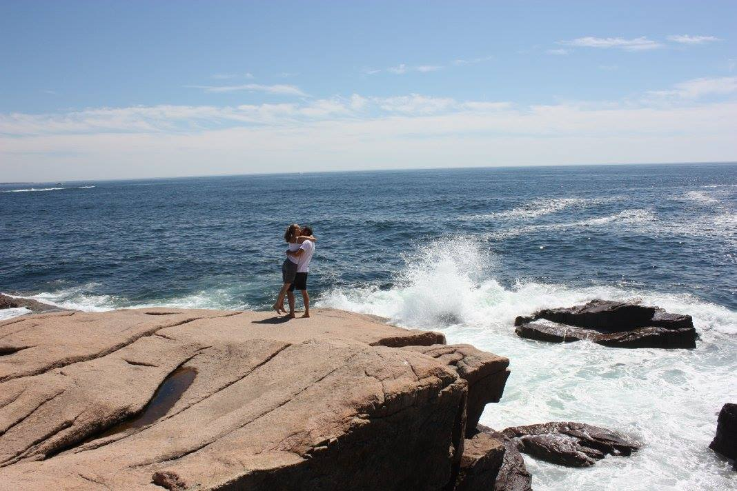 A romantic kiss on the cliffs of Acadia National Park.