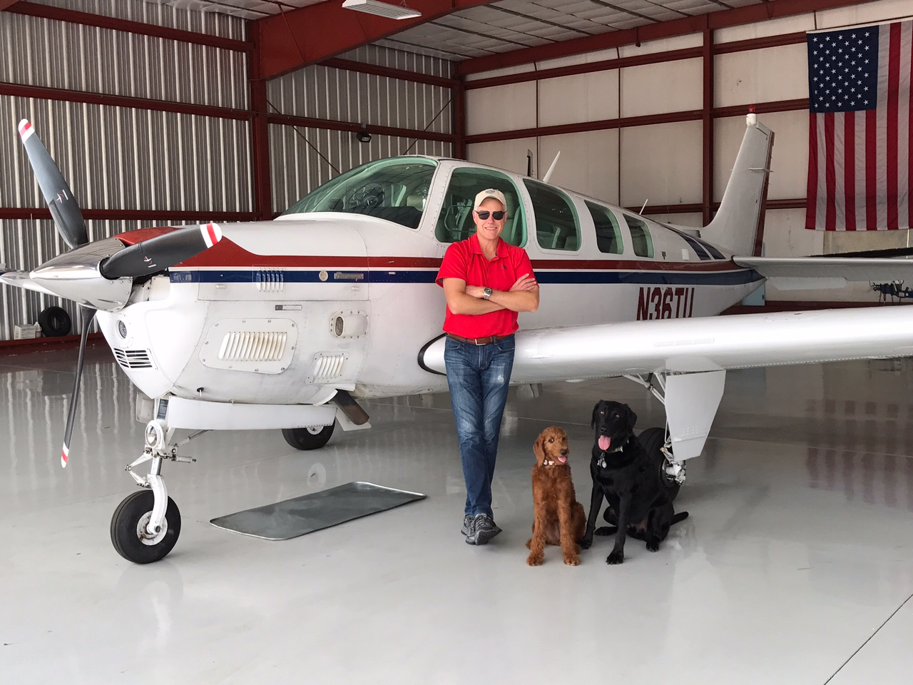 Miles stands next to his plane with his dogs by his side.