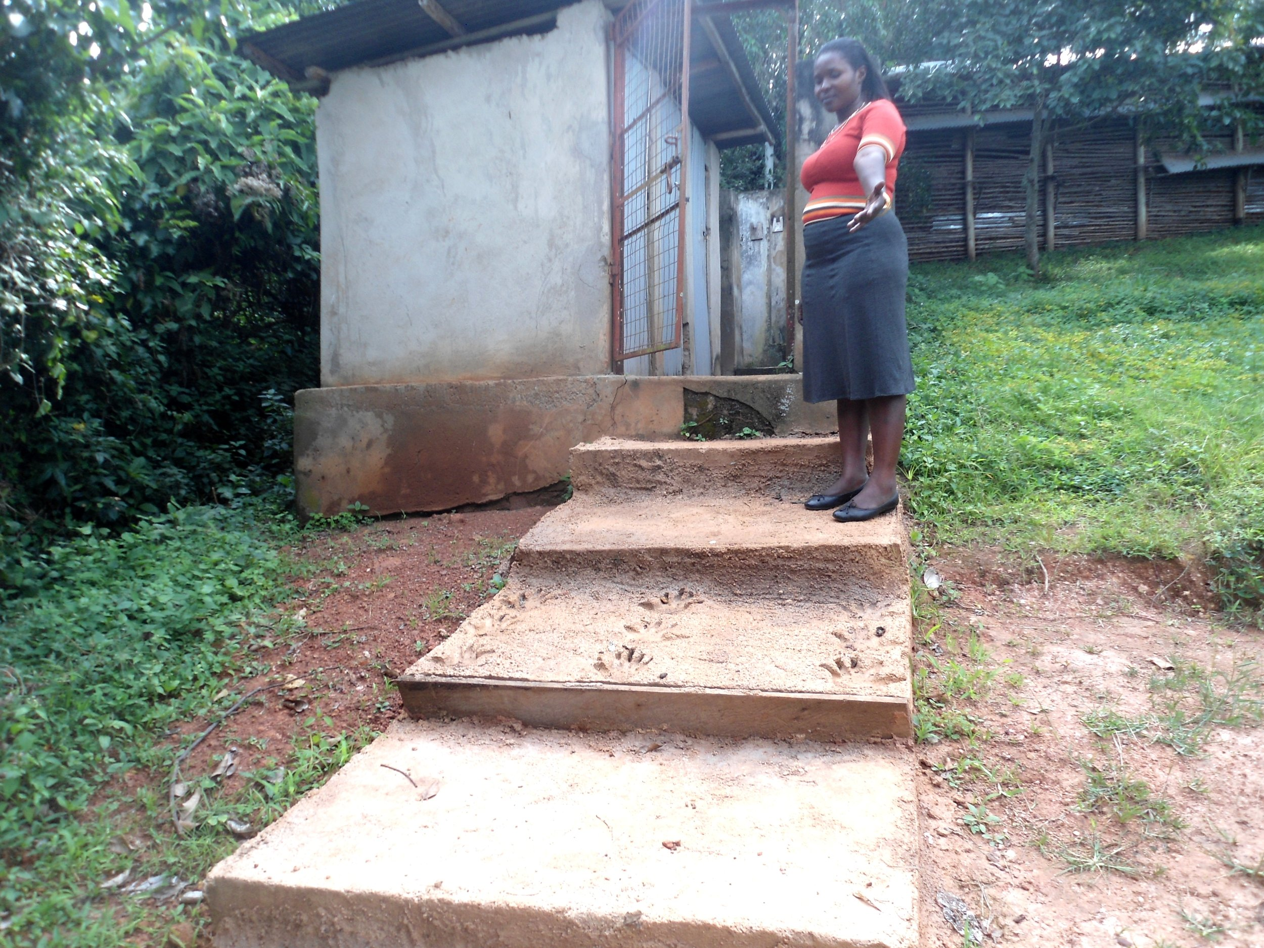 Administrator showing the steps to  the dispensary toilet constructed by DHL.JPG