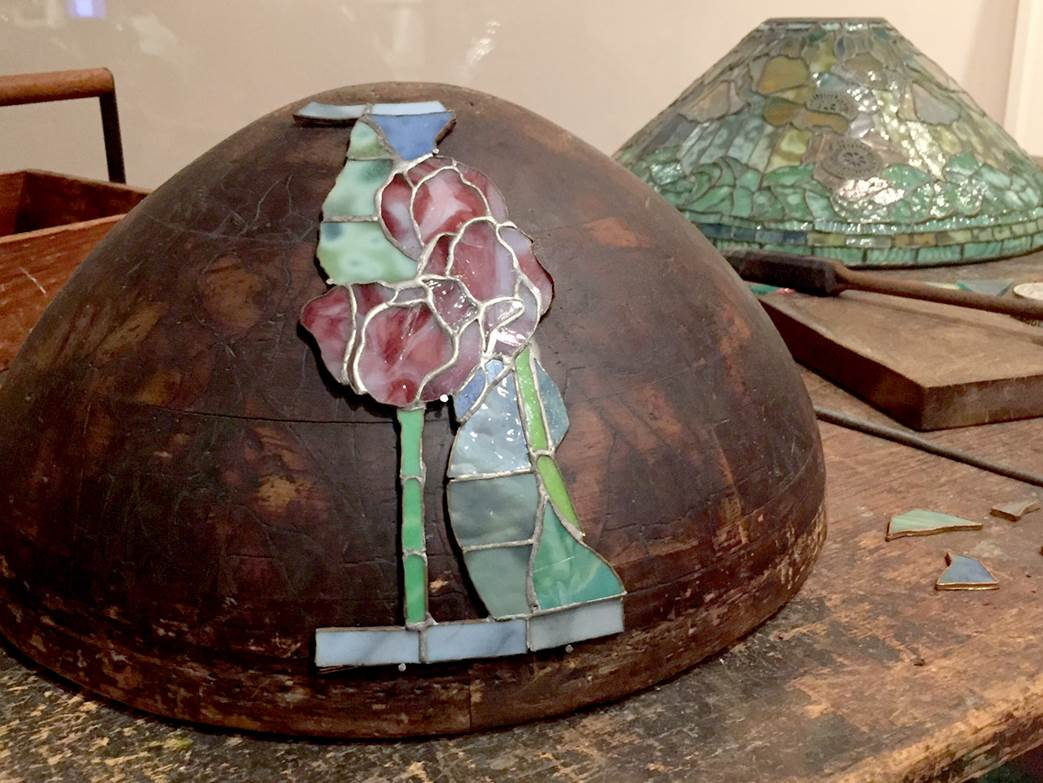A work table from Tiffany Studios showing a lamp form with a shade under construction