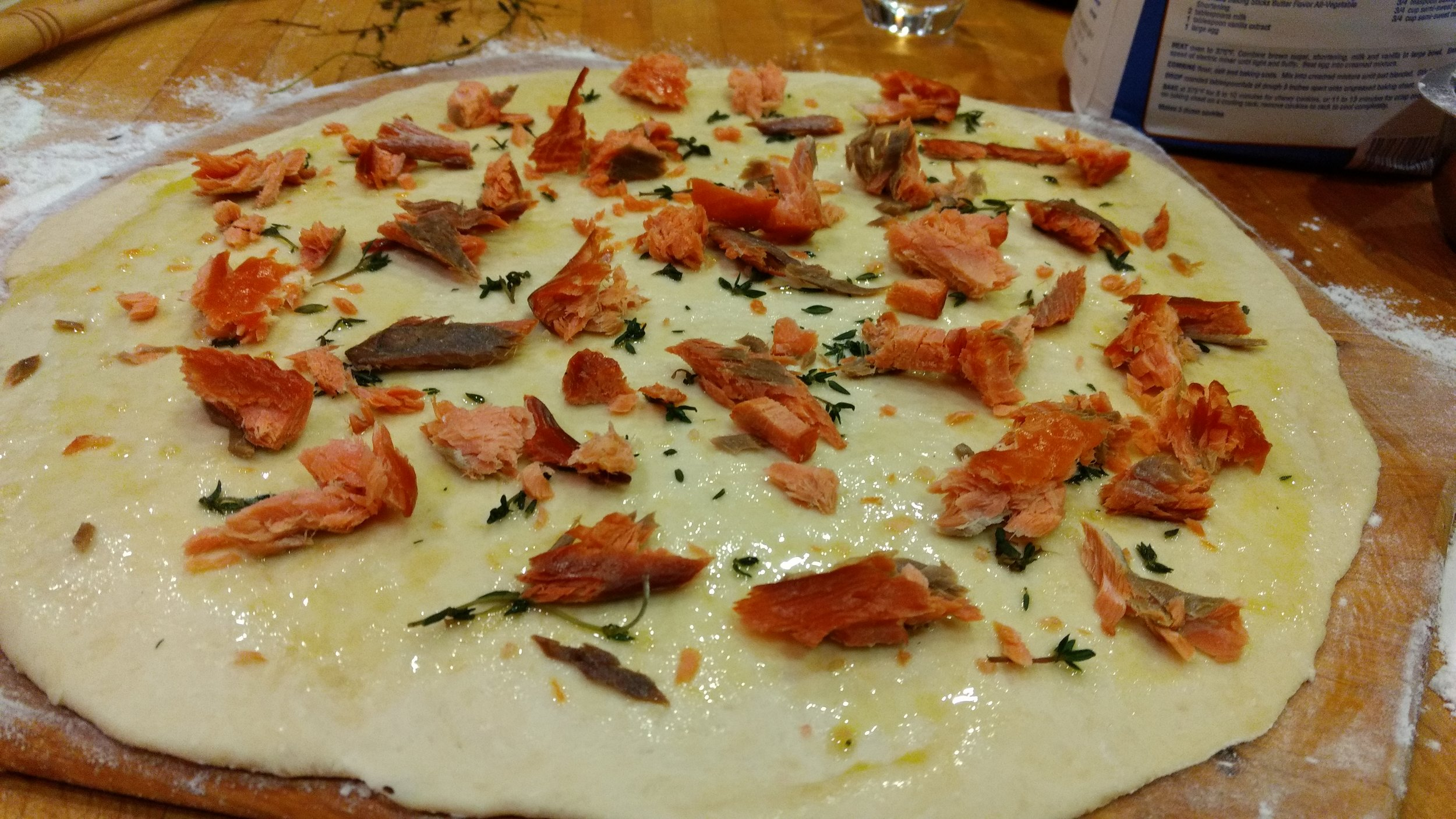 We love pizza made without red sauce. Here we start with olive oil, a little sage, and smoked salmon!