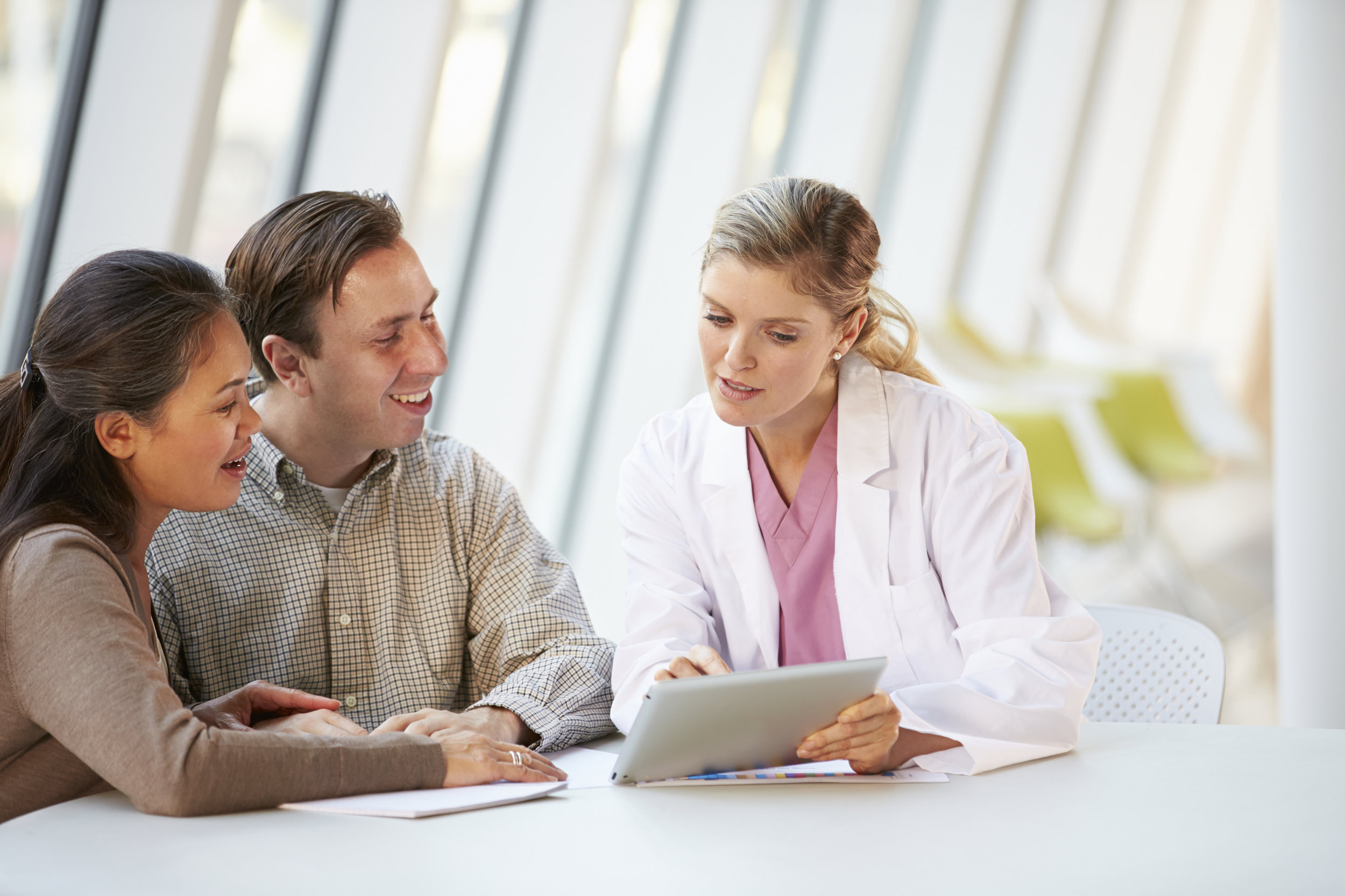Female-Doctor-Using-Digital-Tablet-Talking-With-Patients-000022796590_Double.jpg