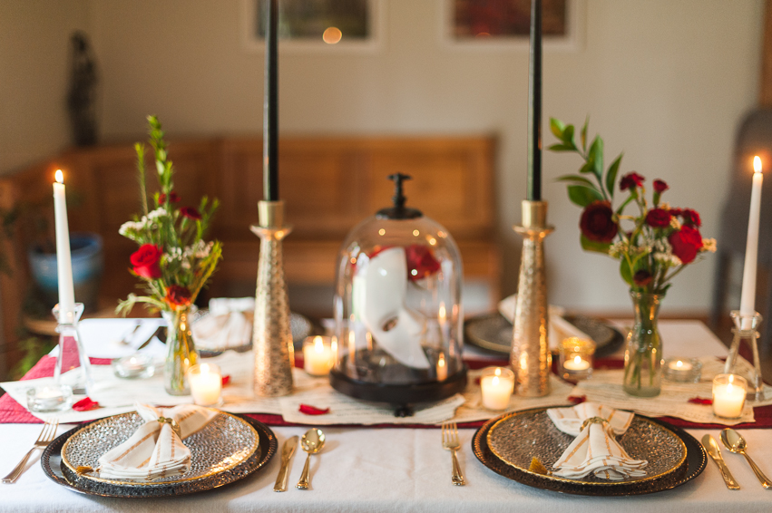 Thrifted vases, sheet music, red table runner. Plates, napkins, clear candlesticks are clearance HomeGoods, tall gold candlesticks are clearance Anthropologie, and the napkin rings and cloche are Halloween clearance from Target.