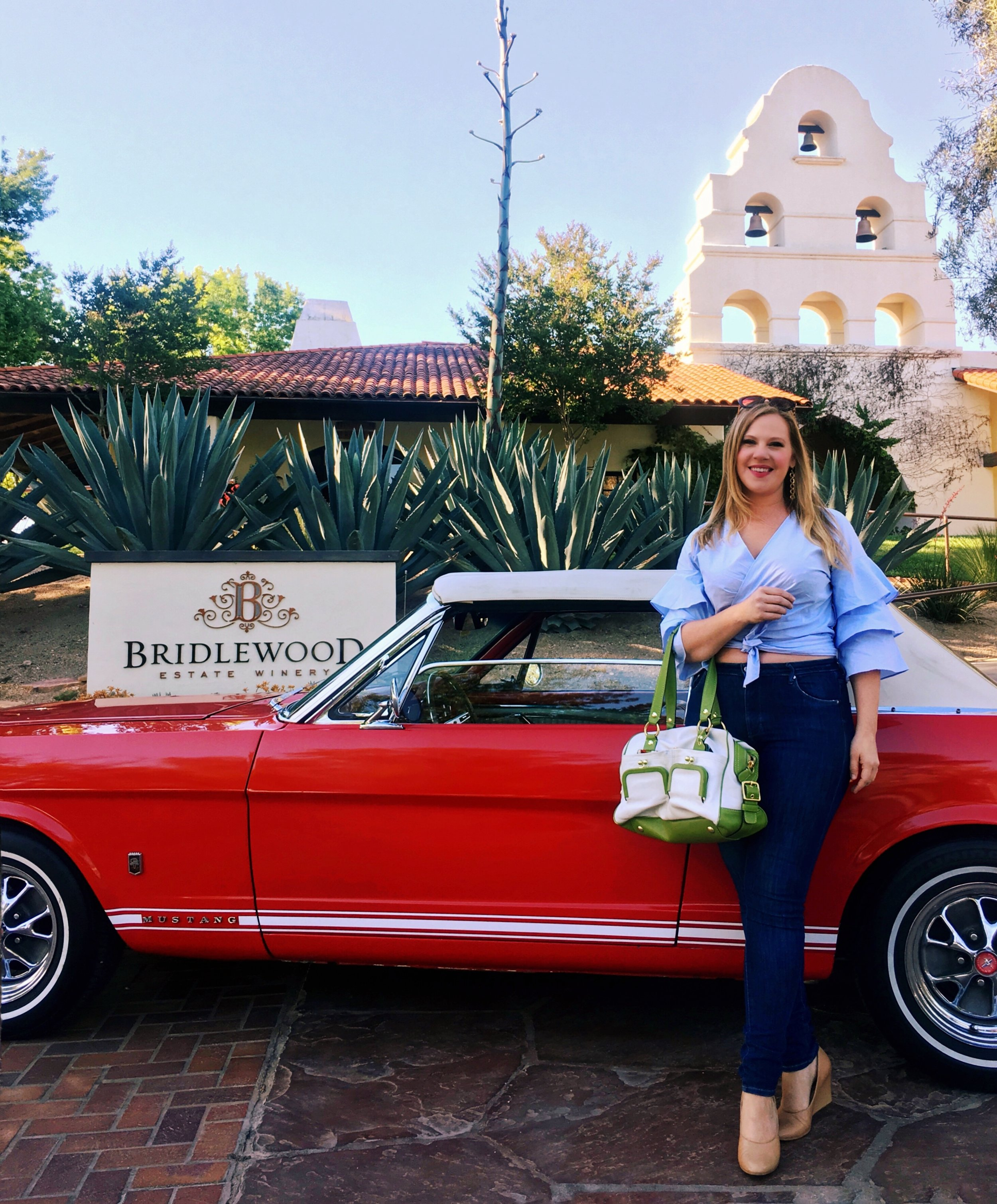 Visiting Bridlewood Estate Winery in Santa Ynez, California. Blonde with vintage red Mustang convertible, classic cars in California, wineries of the Central Coast, Sarah Tracey of The Lush Life, wine travel blog.