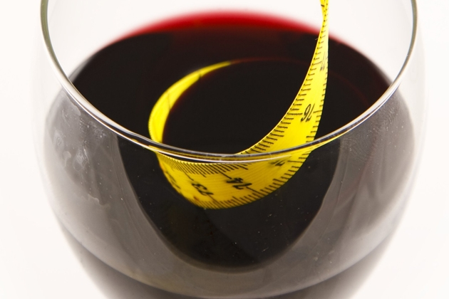 At The Lush Life, we believe that you can and should drink wine on a diet. Red wine glass with tape measure.