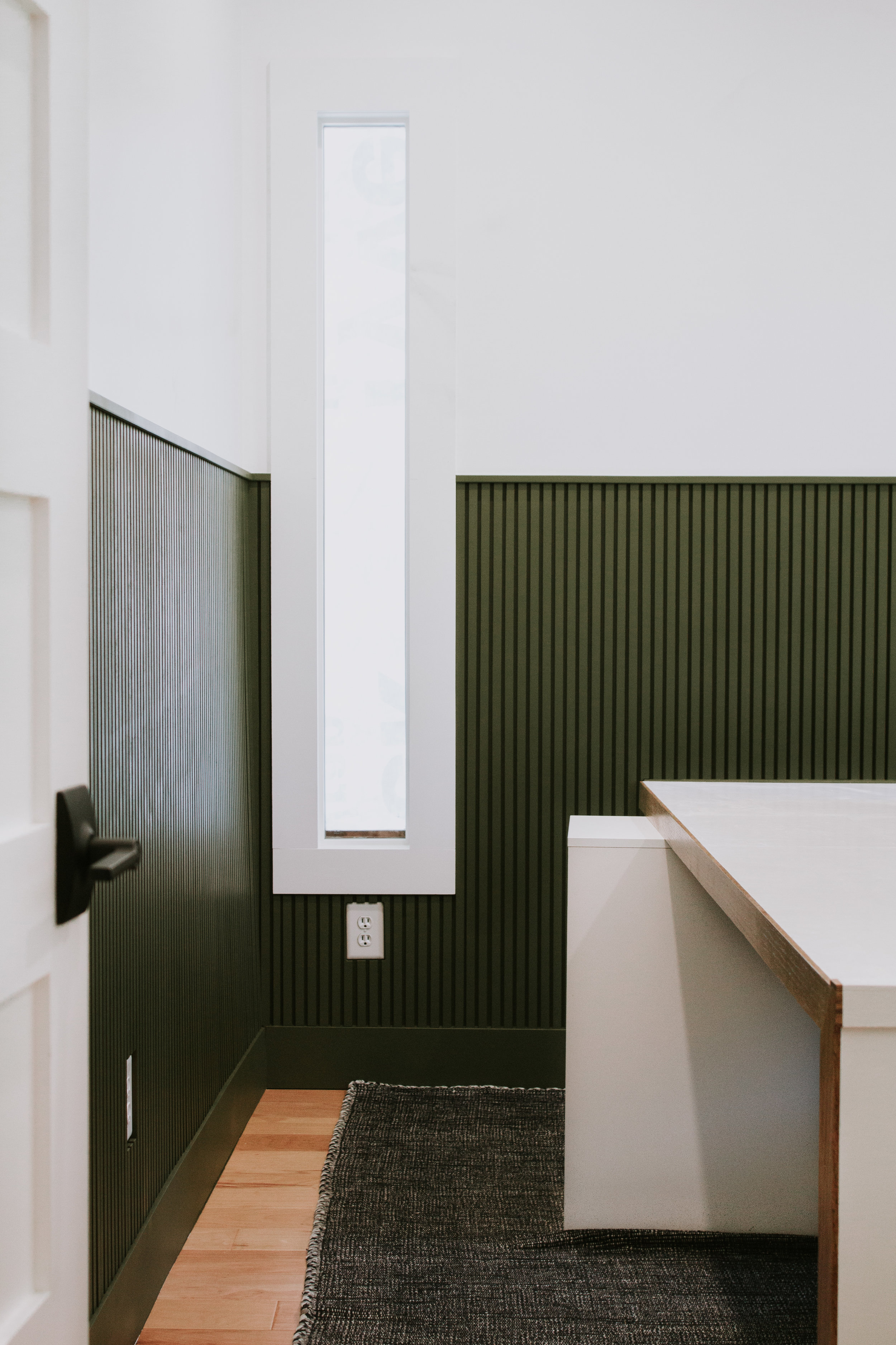 Installing modern wainscoting in our home office. Office makeover by Nadine Stay. Vertical slats painted in a rich hunter green. Full tutorial - how to install modern wainscoting in your home.