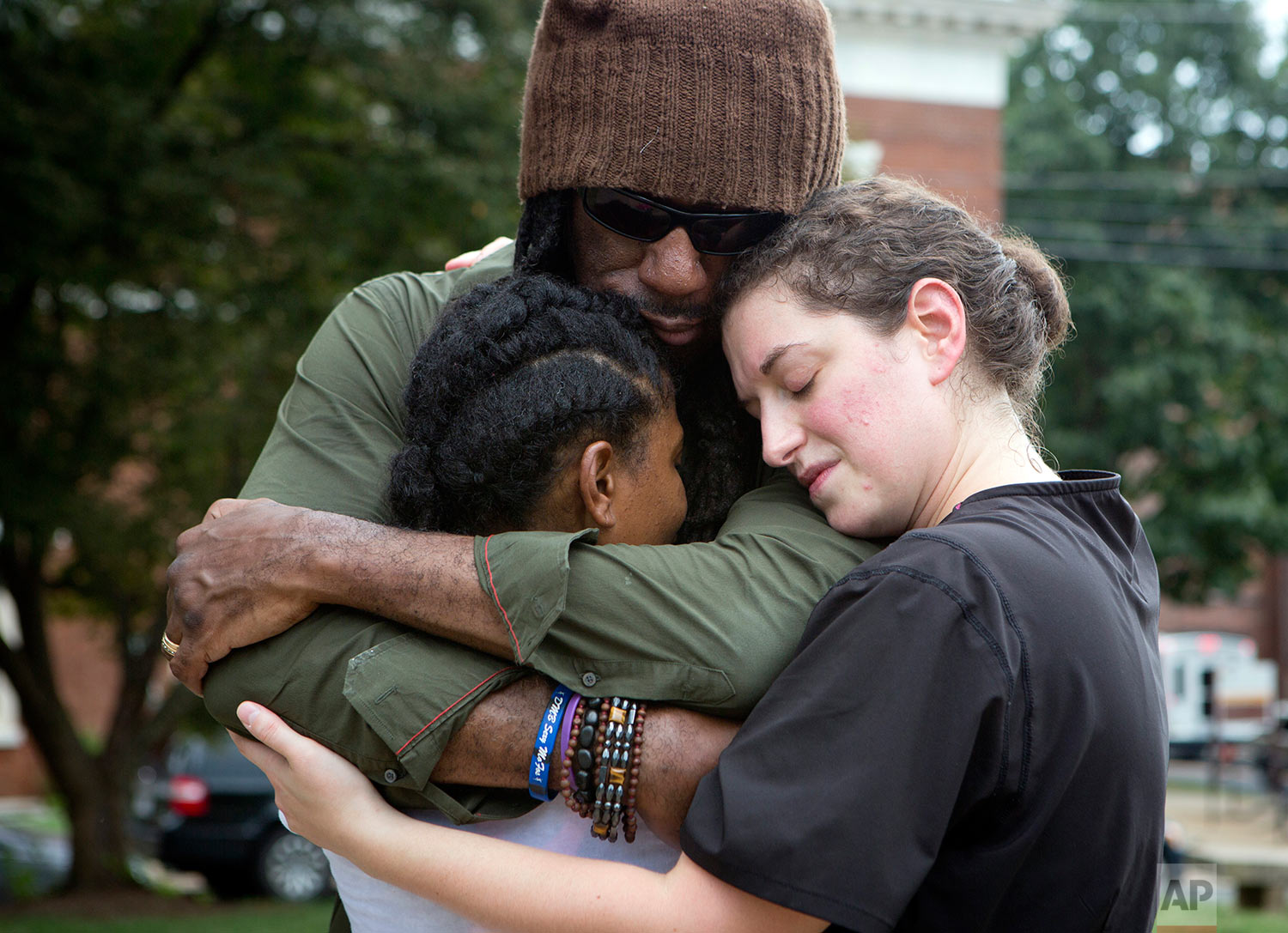 Aaliyah Jones, 38, left, hugs Boyd Tinsley, of the Dave Matthews Band and Amy Hastings, 29, all of Charlottesville, at the base of the Confederate General Robert E. Lee monument in Emancipation Park Tuesday, Aug. 15, 2017, in Charlottesville, Va. The deadly rally by white nationalists in Charlottesville, over the weekend is accelerating the removal of Confederate statues in cities across the nation. (AP Photo/Julia Rendleman)