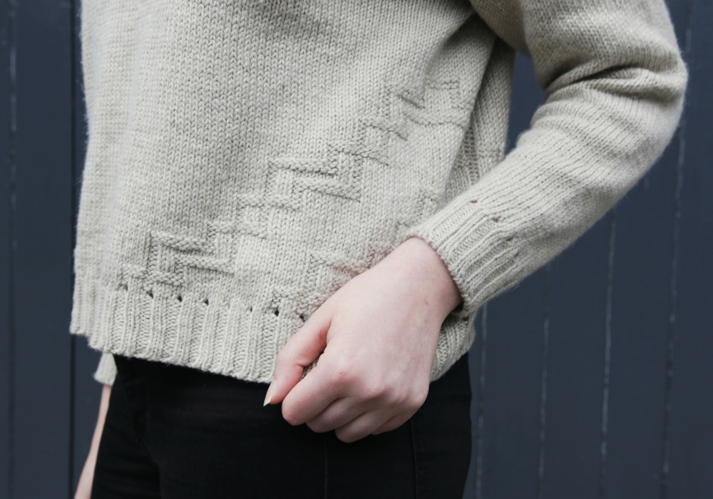 The geometric stitch pattern travels across the sides of the sweater using only knits and purls to create a texture in relief.