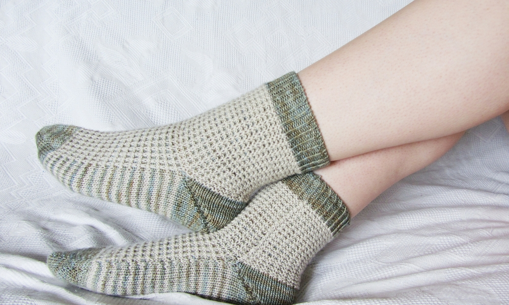 They feature a slipped stitch waffle across the top of the foot and around the ankle. The sole of the sock is striped.