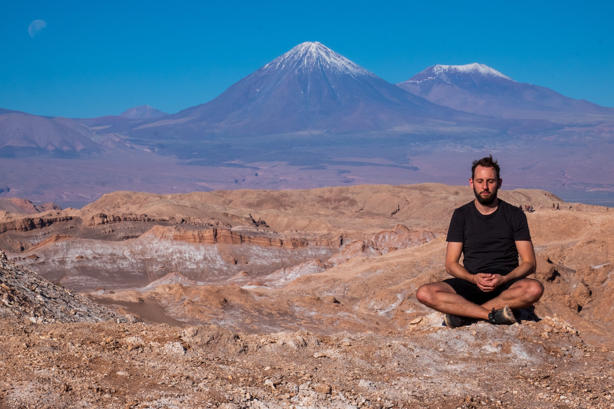 Rory meditating in the Atacama Desert in Chile with Chiliques Volcano in the background