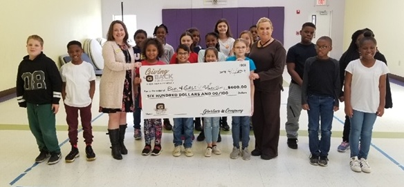 Stacy Adams, Ghertner & Company Director of Human Resources presents the check to these deserving young people and leaders.