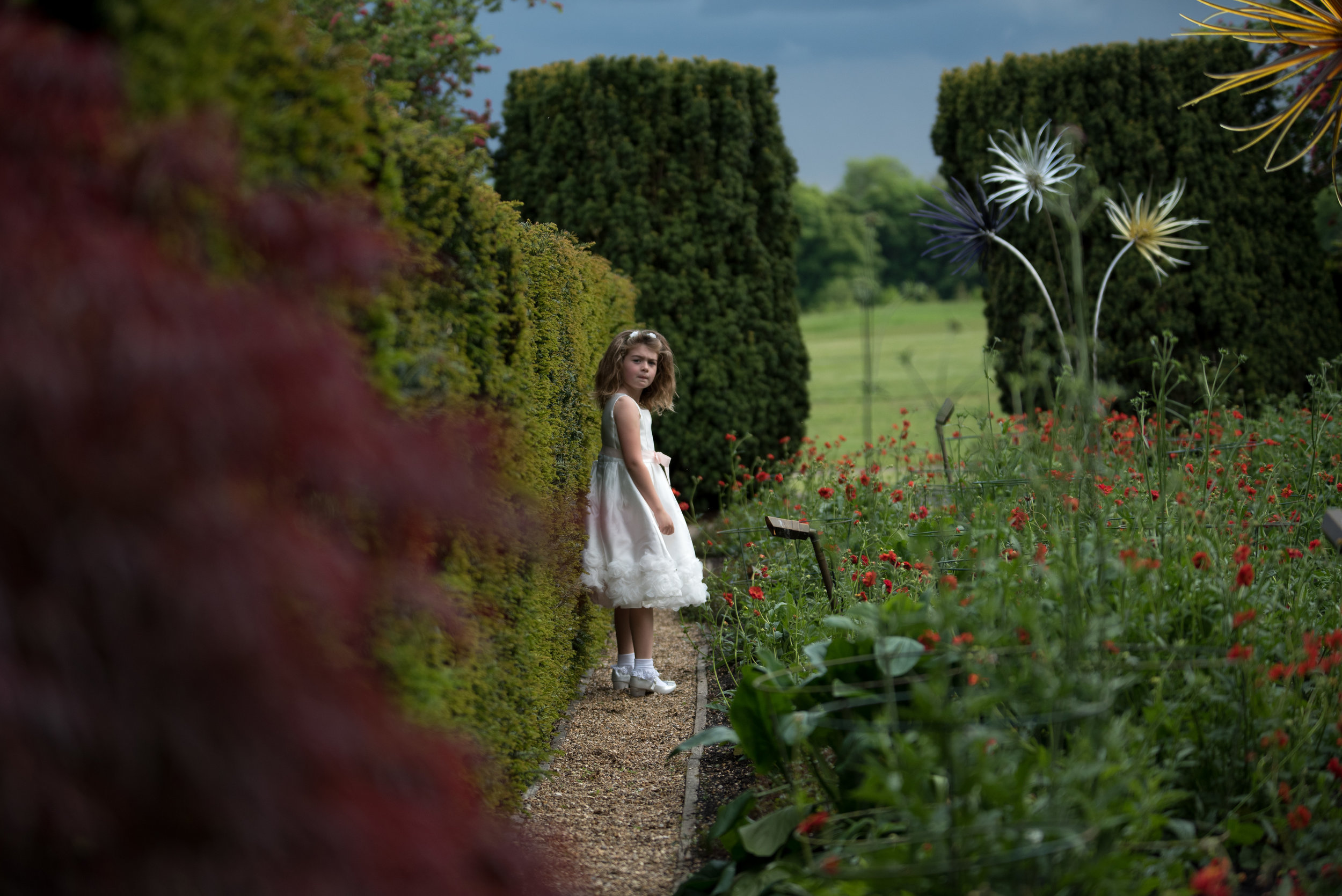 Bridesmaid in formal garden of The Grove Hotel