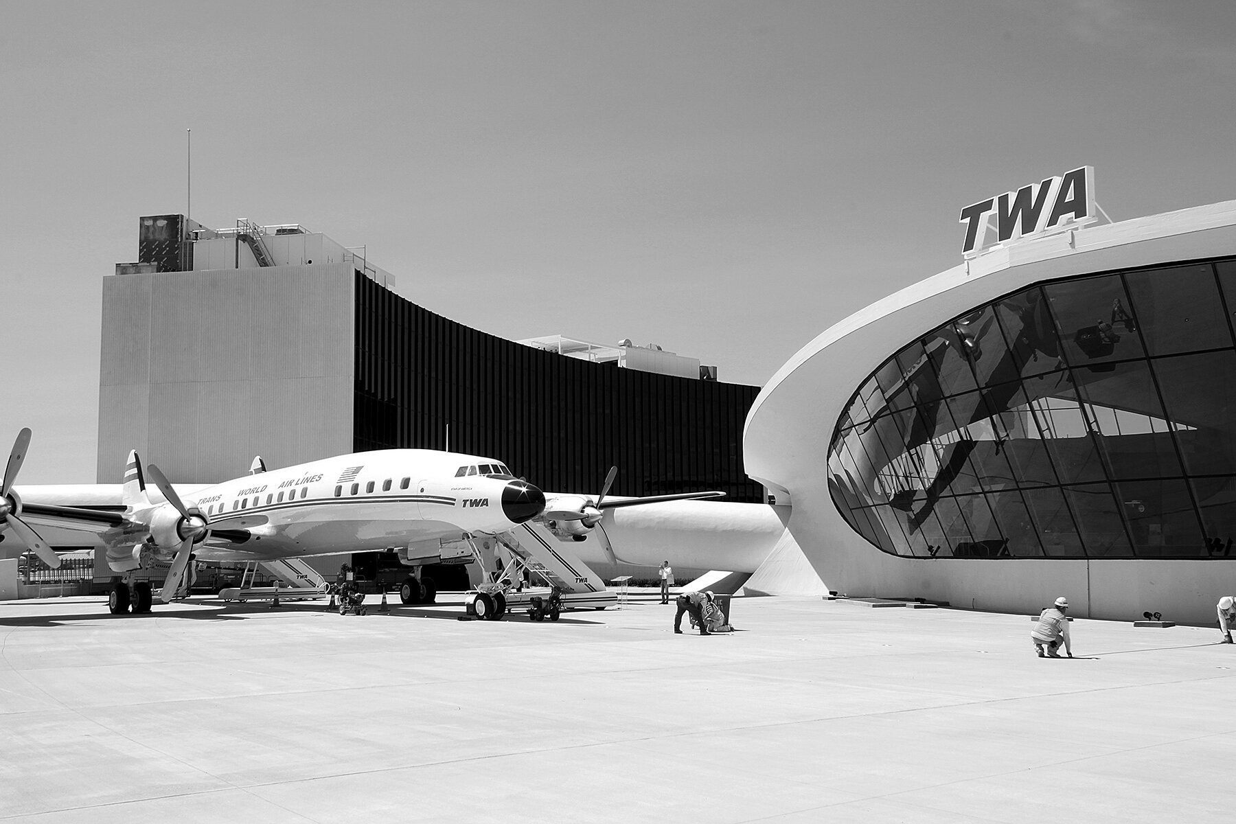 The restored Lockheed Constellation is a museum piece cum bar, grounded on a faux tarmac. Photo: Patrick Templeton. Top: The TWA logo greets visitors arriving at the new hotel. Photo: David Mitchell. Courtesy TWA Hotel.