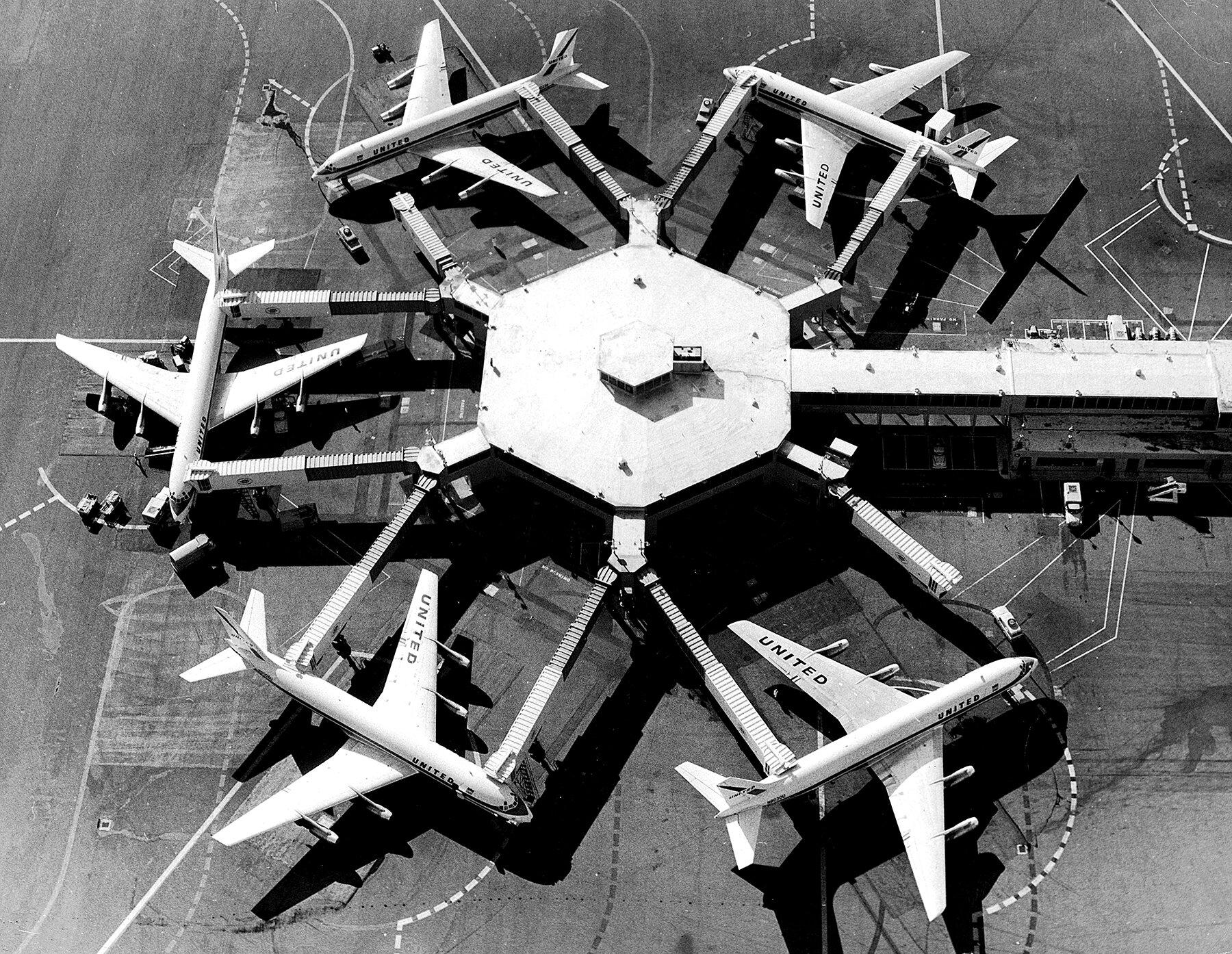 United Air Lines DC-8 jets parked at tandem aero-gangplank loading bridges, San Francisco International Airport, circa 1962.