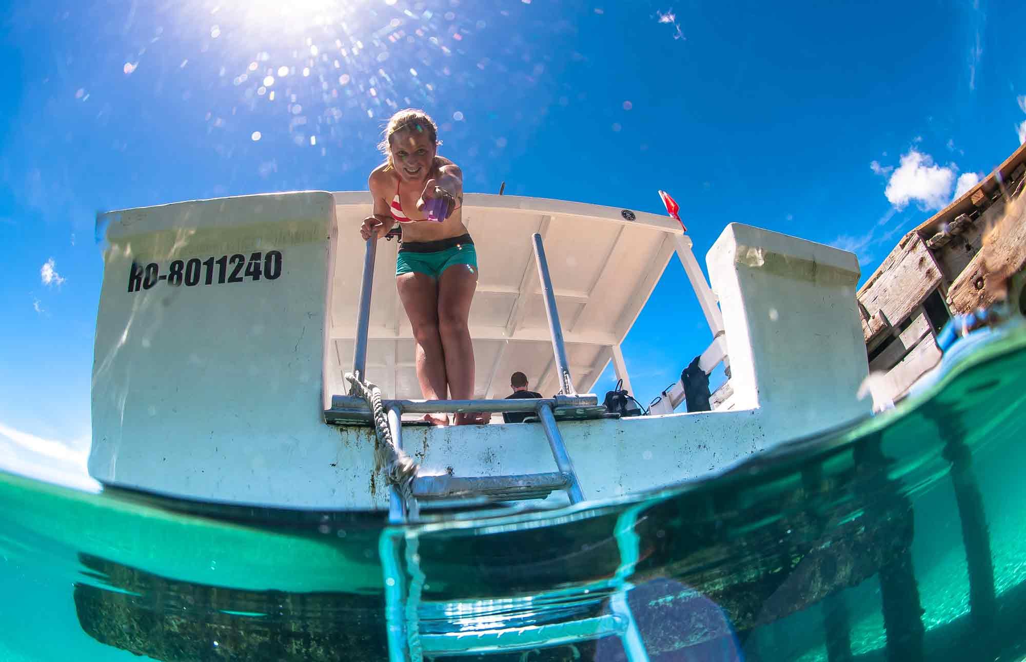Divemaster in training helping a diver with their camera, Roatan, Honduras