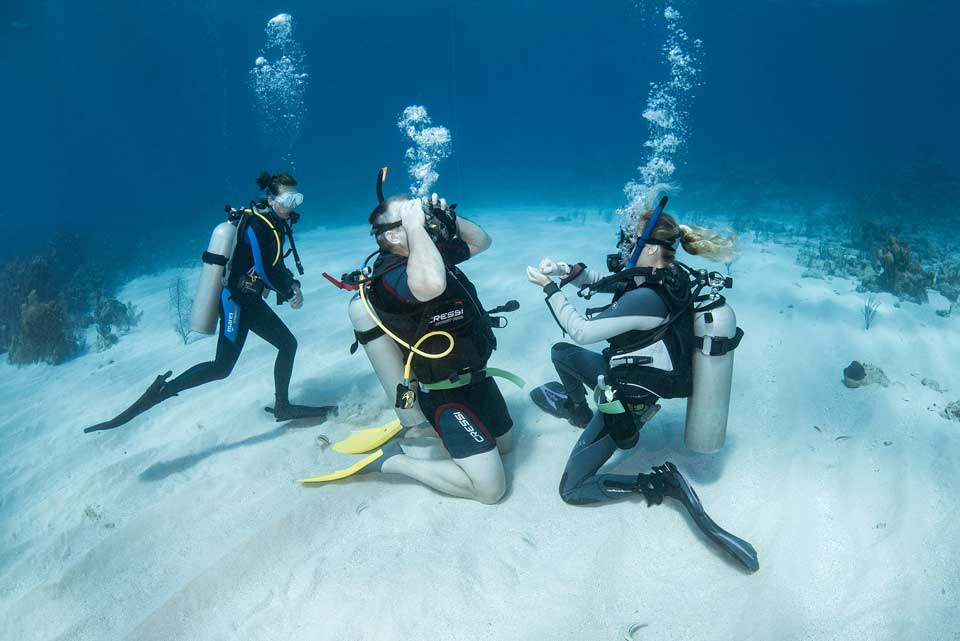 A PADI Instructor working with a student during an open water diver course.