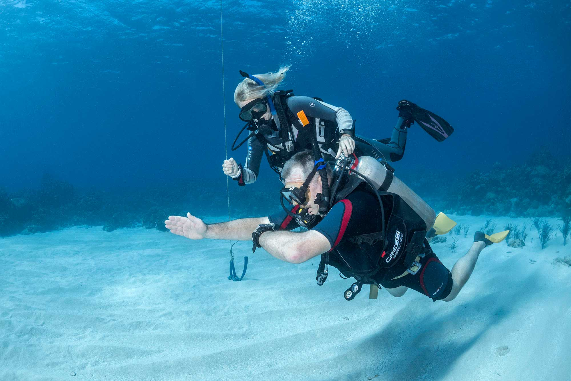 Instructor development course candidate teaching navigation skills to a student scuba diver