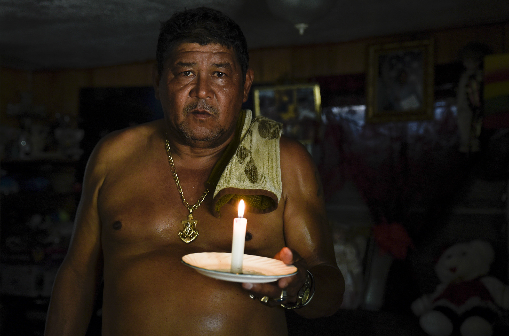 "Fifty-nine-year-old Lake Worth resident Mario Velasquez poses for a portrait holding a candle, his main source of light at night, inside his Orange Grove Mobile Home Park residence in Lake Worth, Fla., on Tuesday, September 12, 2017. Velasquez said the neighborhood had been without power since Friday, two days before Hurricane Irma impacted the county. ""One feels bothered because nobody pays attention to us,"" he said. ""Because we're poor we don't get as much attention."""