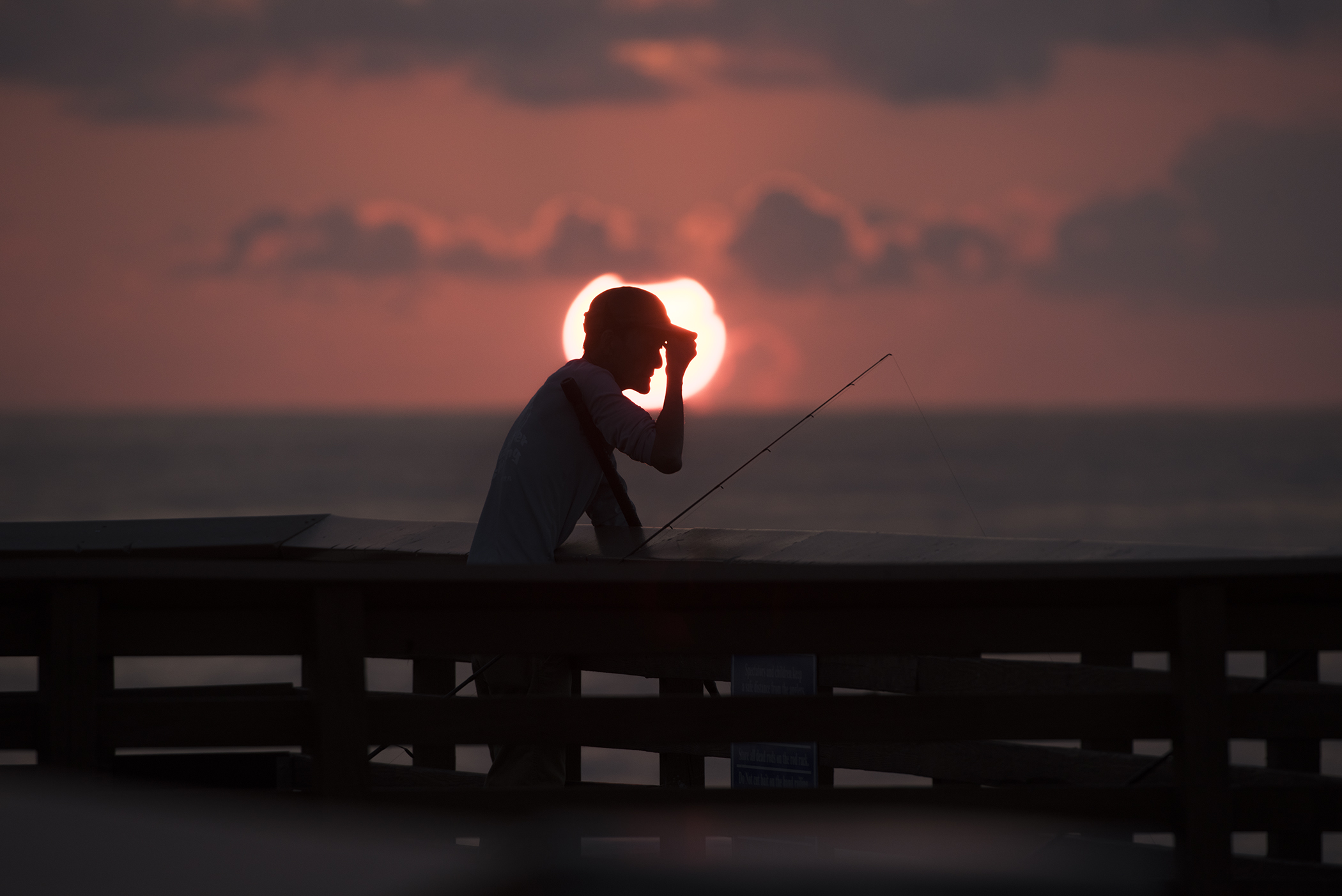 A man who asked not to be identified adjusts his cap while fishing at the Juno Beach Fishing Pier at sunrise Wednesday, September 20, 2017