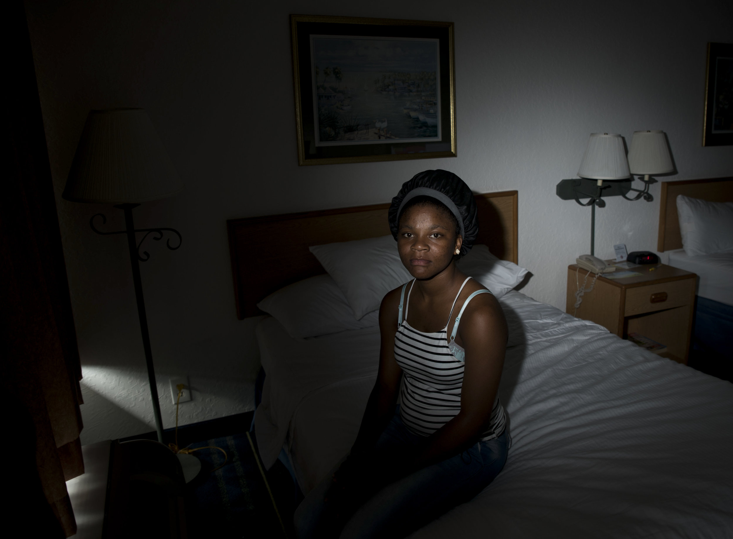 "Tranice Smith, 19, of Riviera Beach, poses for a portrait in the motel she's been living in ever since her ex-boyfriend trapped her three children in her apartment and burned the home down. The three infants survived, but Smith knows what she would do to the man who fathered two of her children. ""He can't swim. I would push him in a pool."""