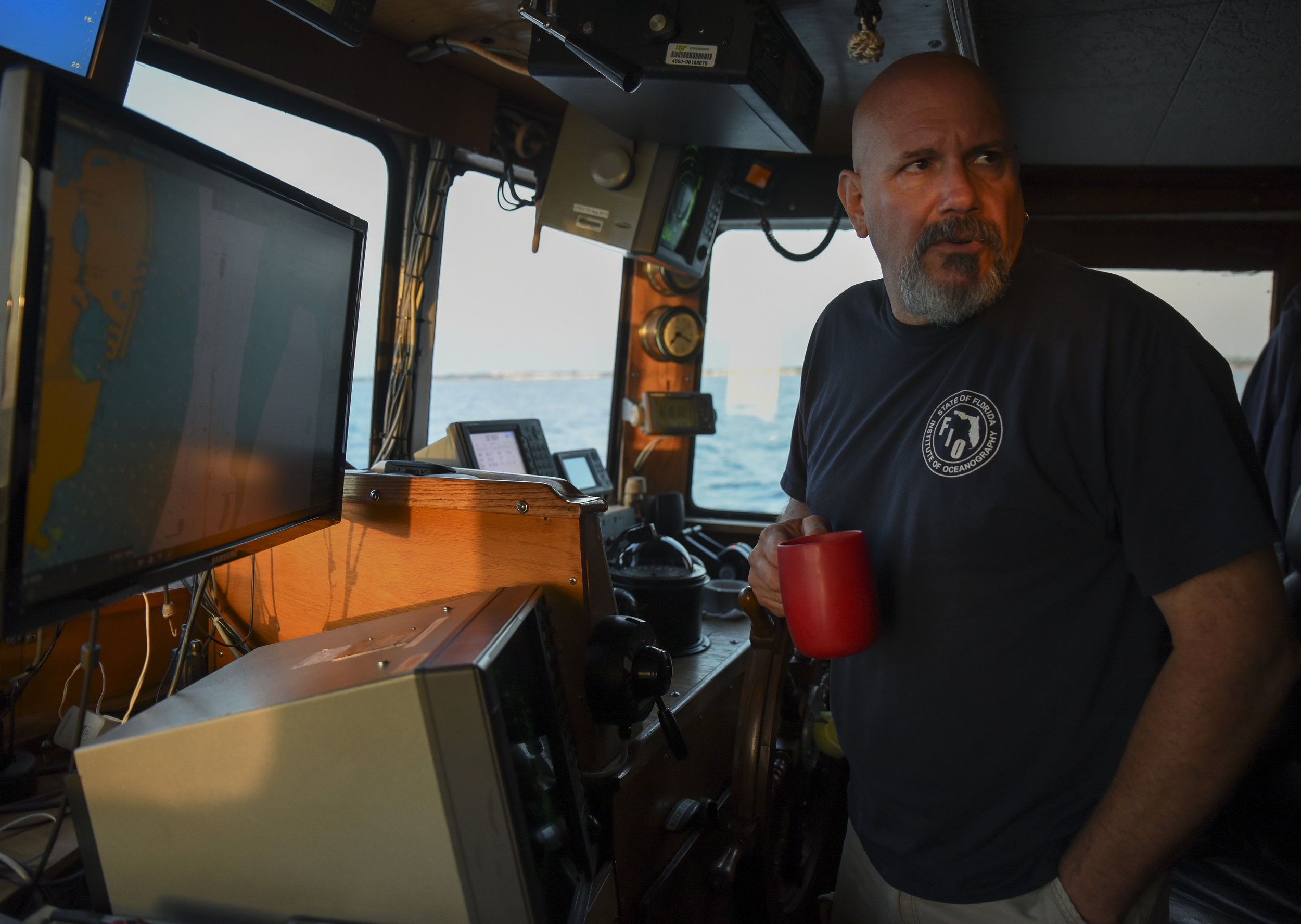 Captain Dave Coy, 56, of the R/V Bellows looks across the vessel's bridge while overseeing the boat's journey through the Tampa Bay channel at sunrise during a research cruise on Monday, April 17, 2017. Students and scientists from New College of Florida, the University of North Florida and Mote Marine Laboratory, aboard the research vessel worked to catch and release a variety of shark species, outfitting them with trackers to study their coastal habits.