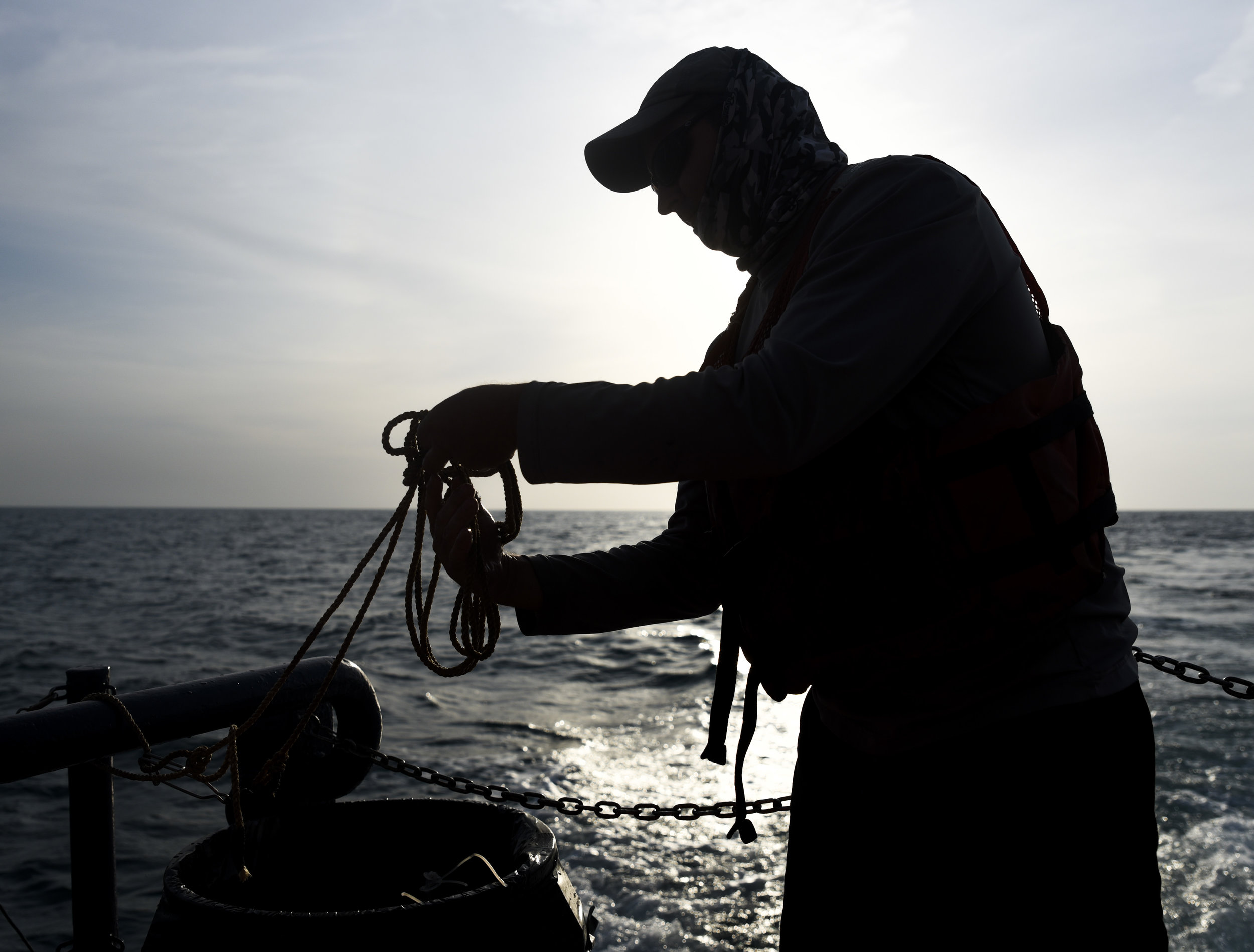 Senior Mote Marine Lab biologist Jack Morris ties up a coil of rope after work aboard the R/V Bellows is done for the day.