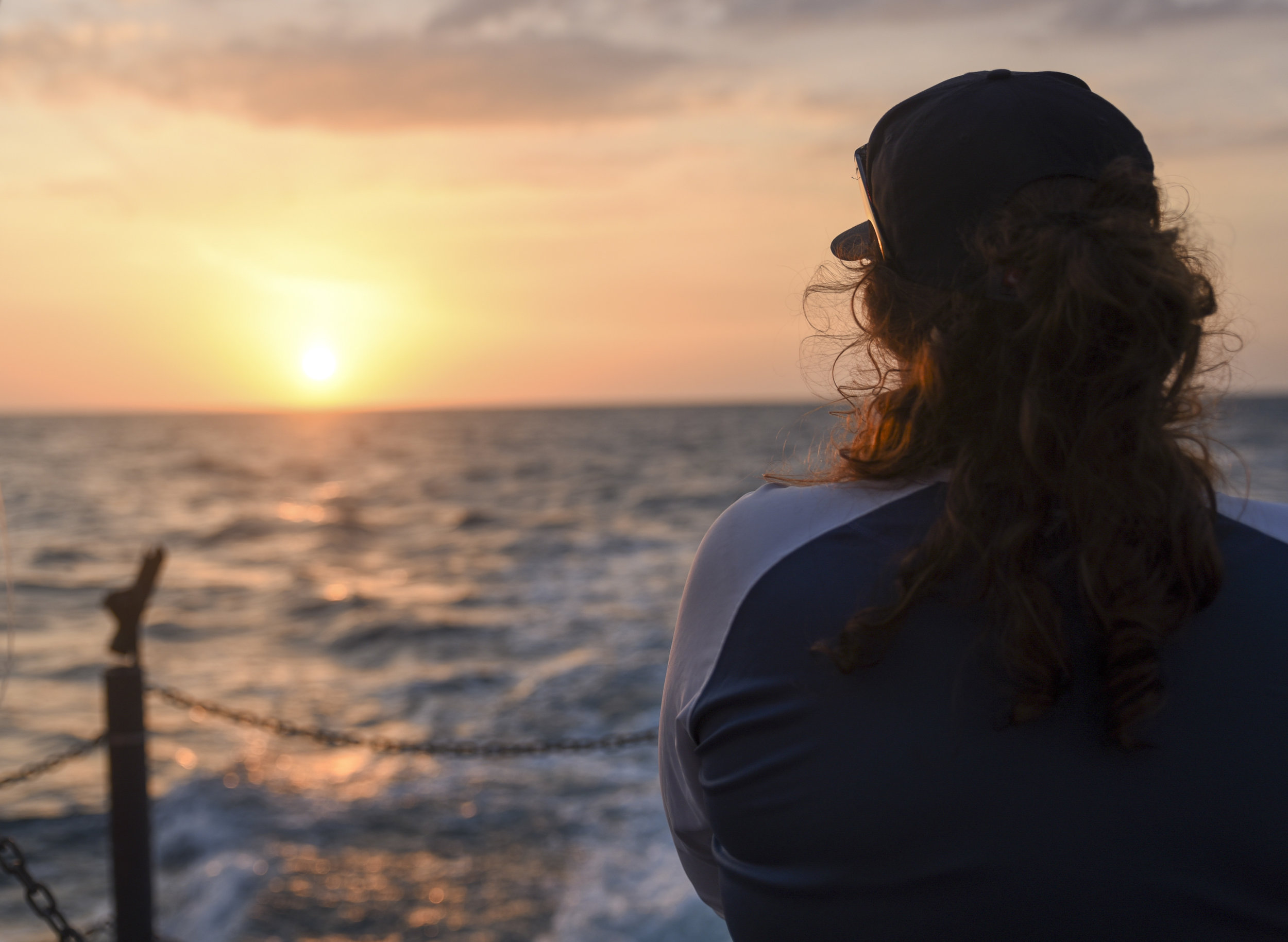 Marlo Leikam, a 21-year-old junior at the New College of Florida, watches the sun set after work is done for the day.