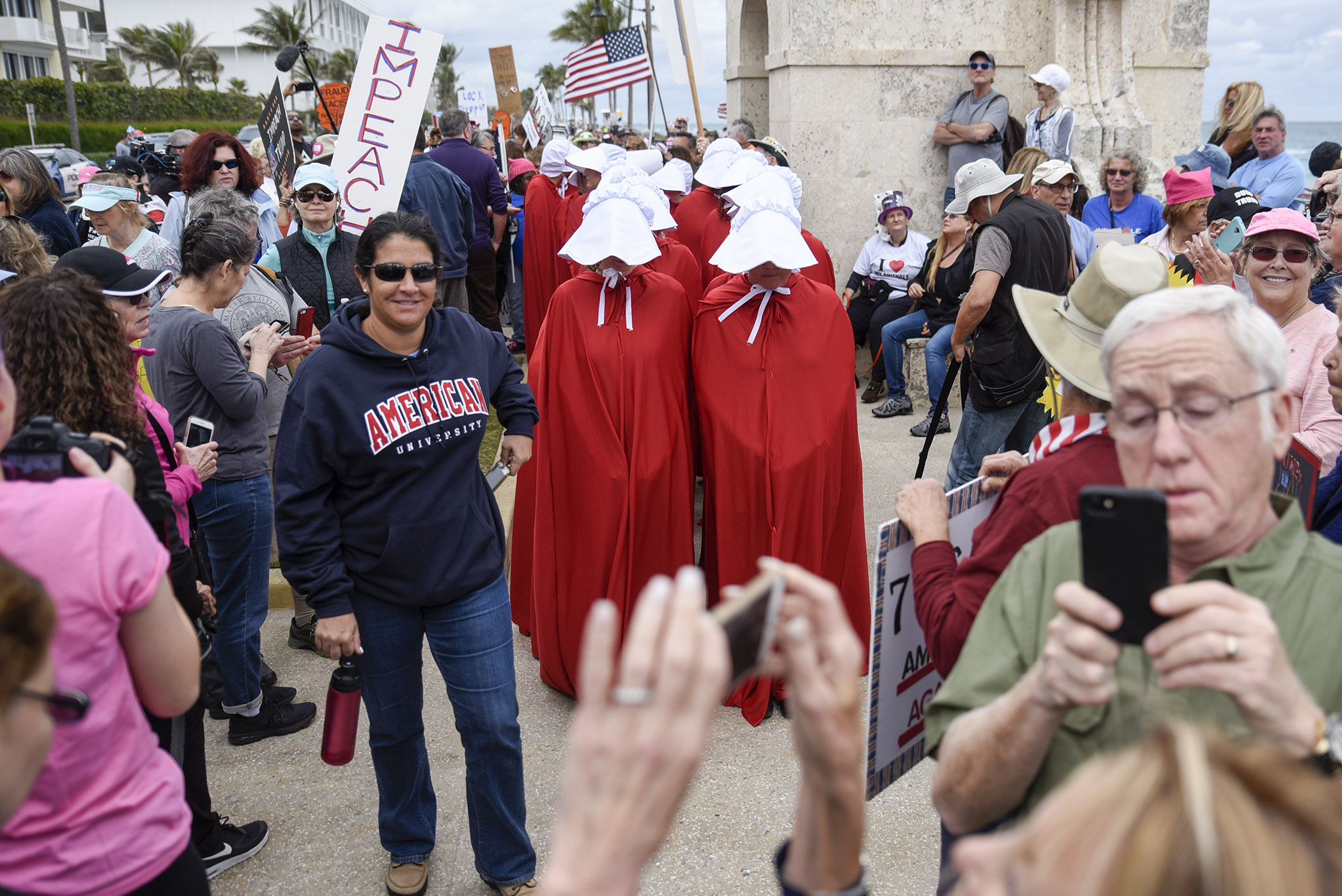 "Trump protestors dressed as Handmaids from ""The Handmaid's Tale"" stand underneath the Clock Tower on South Ocean Boulevard before the start of the ""Impeachment March to Mar-A-Largo"" in Palm Beach. Hundreds of participants gathered in Palm Beach to march towards Mar-A-Largo and protest President Trump on the day marking the first year anniversary of his presidency"