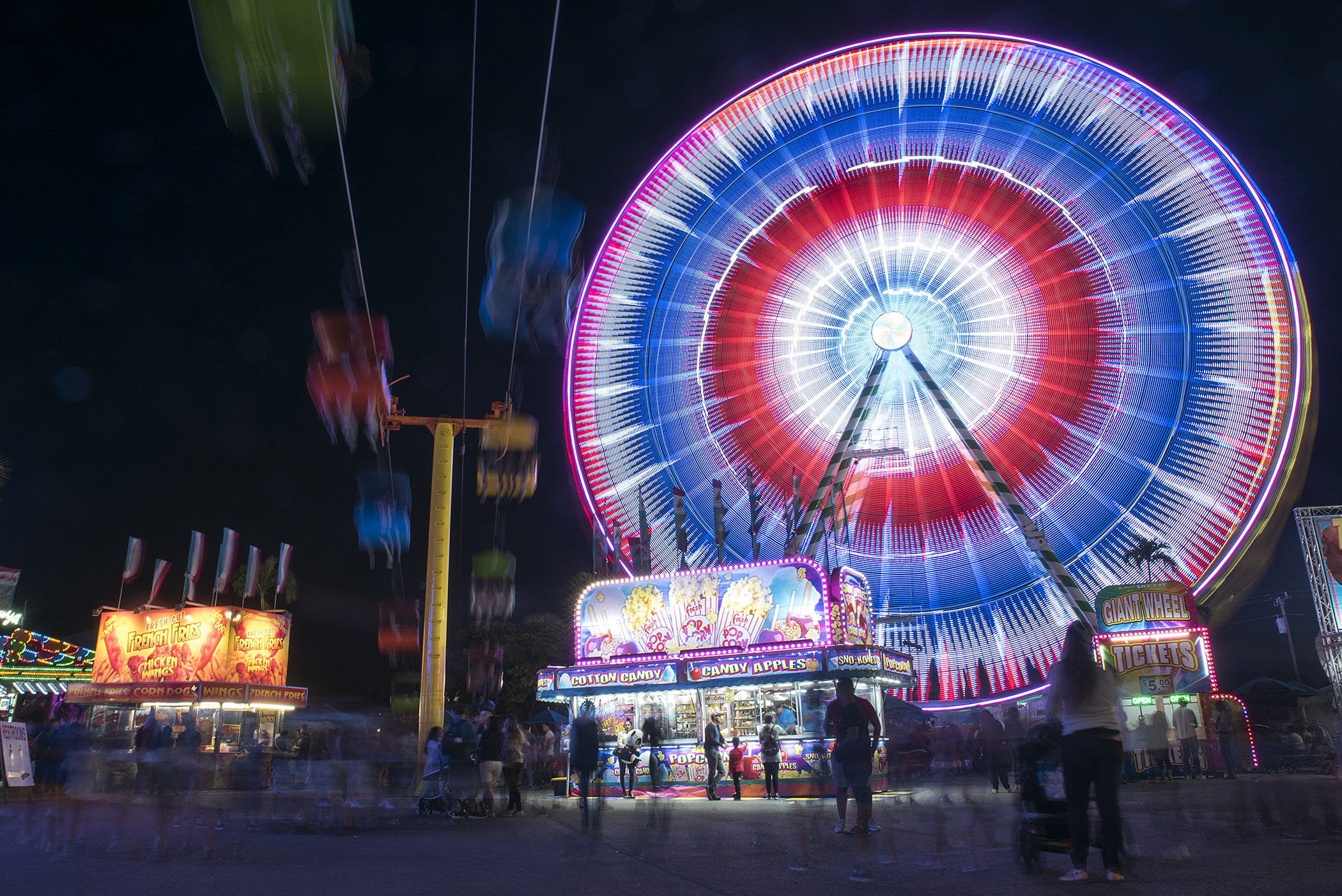 South Florida Fair guests are seen walking underneath the gondola and Ferris wheel rides after dark at the South Florida Fair in West Palm Beach, FL. Thousands of visitors come to the South Florida Fair to play games, eat food and see attractions during the fair's 16-day run.