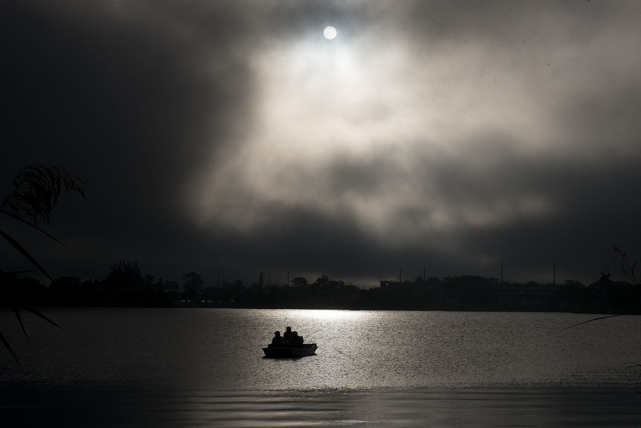 A trio of fisherman are seen in their boat on the Lake Osborne water at sunrise in James Prince Park in Lake Worth, Fla.