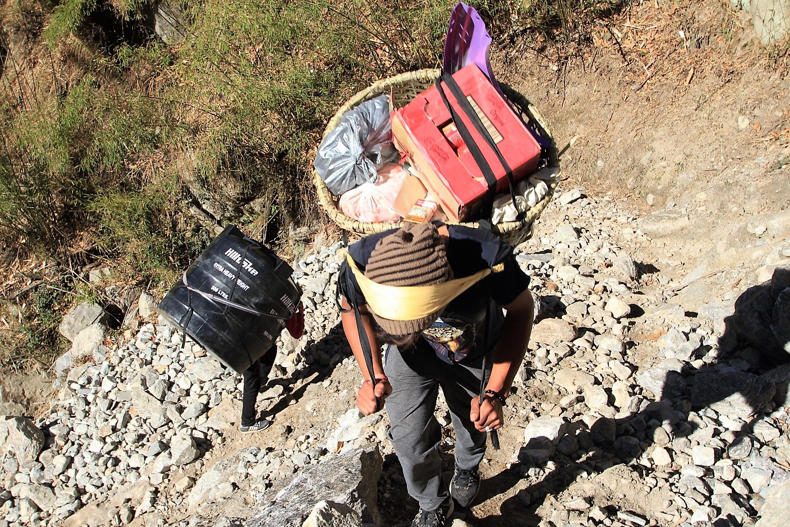 Porters carrying goods and a tank up to Langtang
