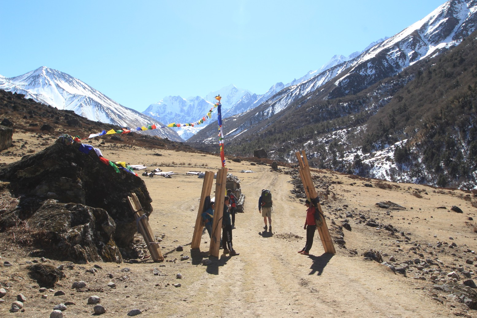 Porters carrying 4x4 posts up the valley
