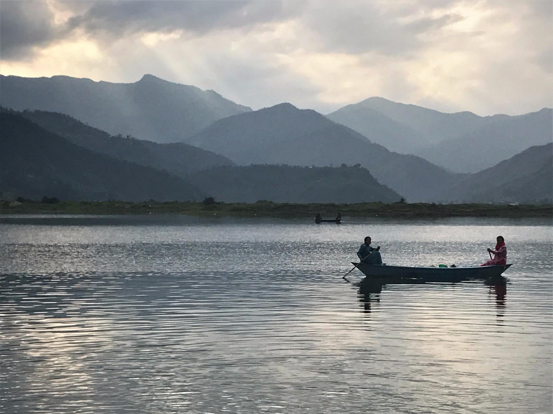Two women fishing at sunset on Fewa Lake