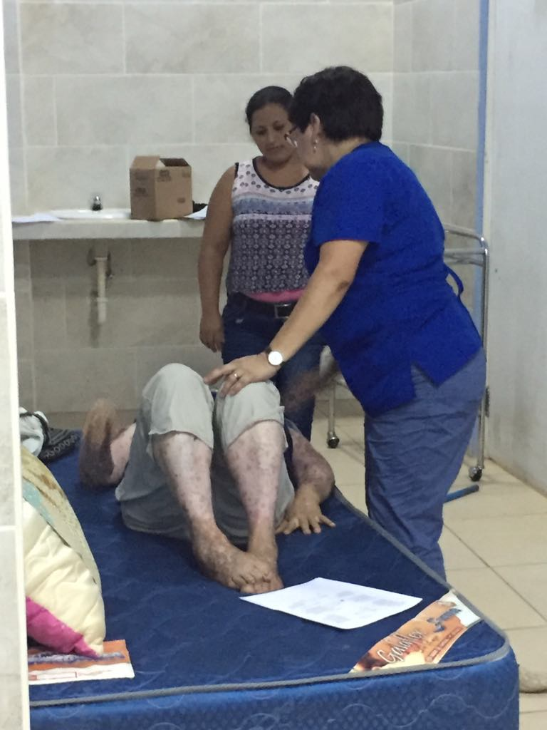 helping a patient with some exercises to help in easing pain in her lower back.
