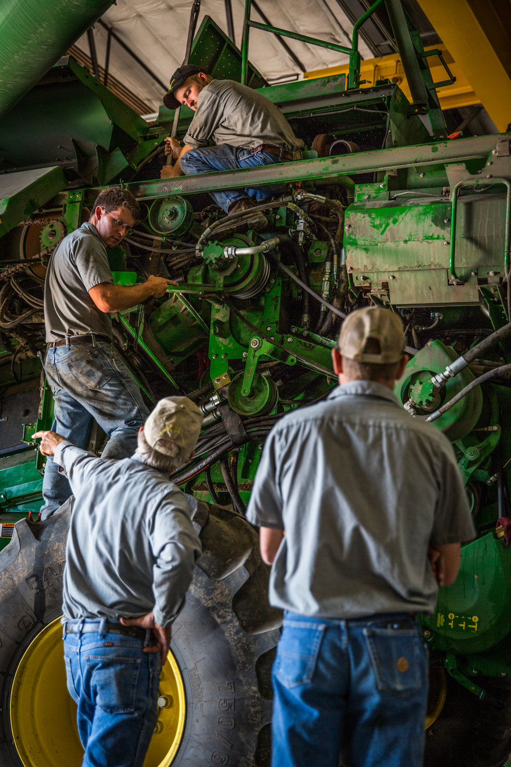 Service technicians work on repairing a combine in the Sydenstricker John Deere dealership in Mexico, Missouri on Tuesday, Oct. 4, 2016.