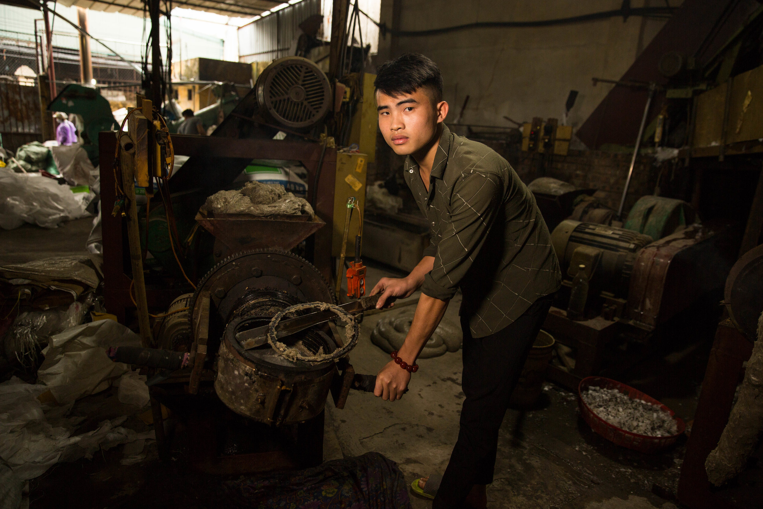 Lo Van Dinh, 21, operates a machine to melt plastics in Minh Khai, Vietnam, on Thursday, Jan. 17, 2019. The village is a hub for recycling both domestic and foreign plastics.
