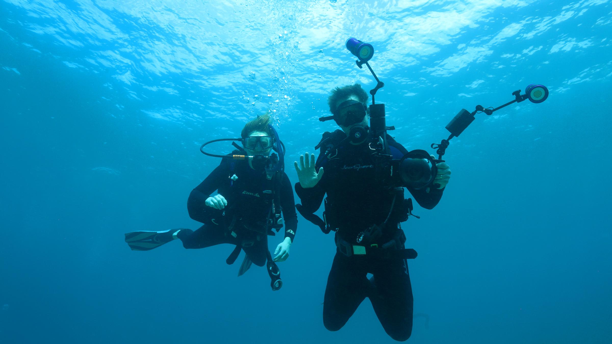 Laura Sams and Robert Sams scuba dive with their video camera.