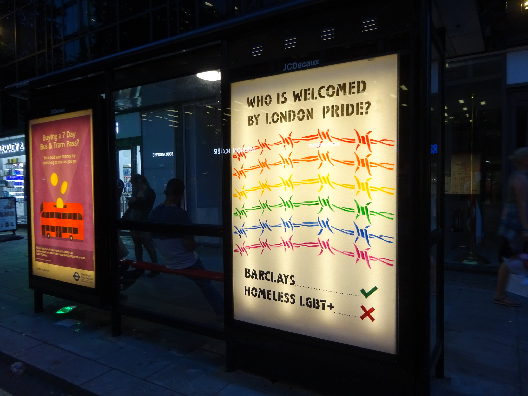 Bus stop adhack by Lesbians and Gays Support the Migrants and Protest Stencil protesting the exclusion of LGBT+ asylum seekers, homeless people and community groups from Pride in London
