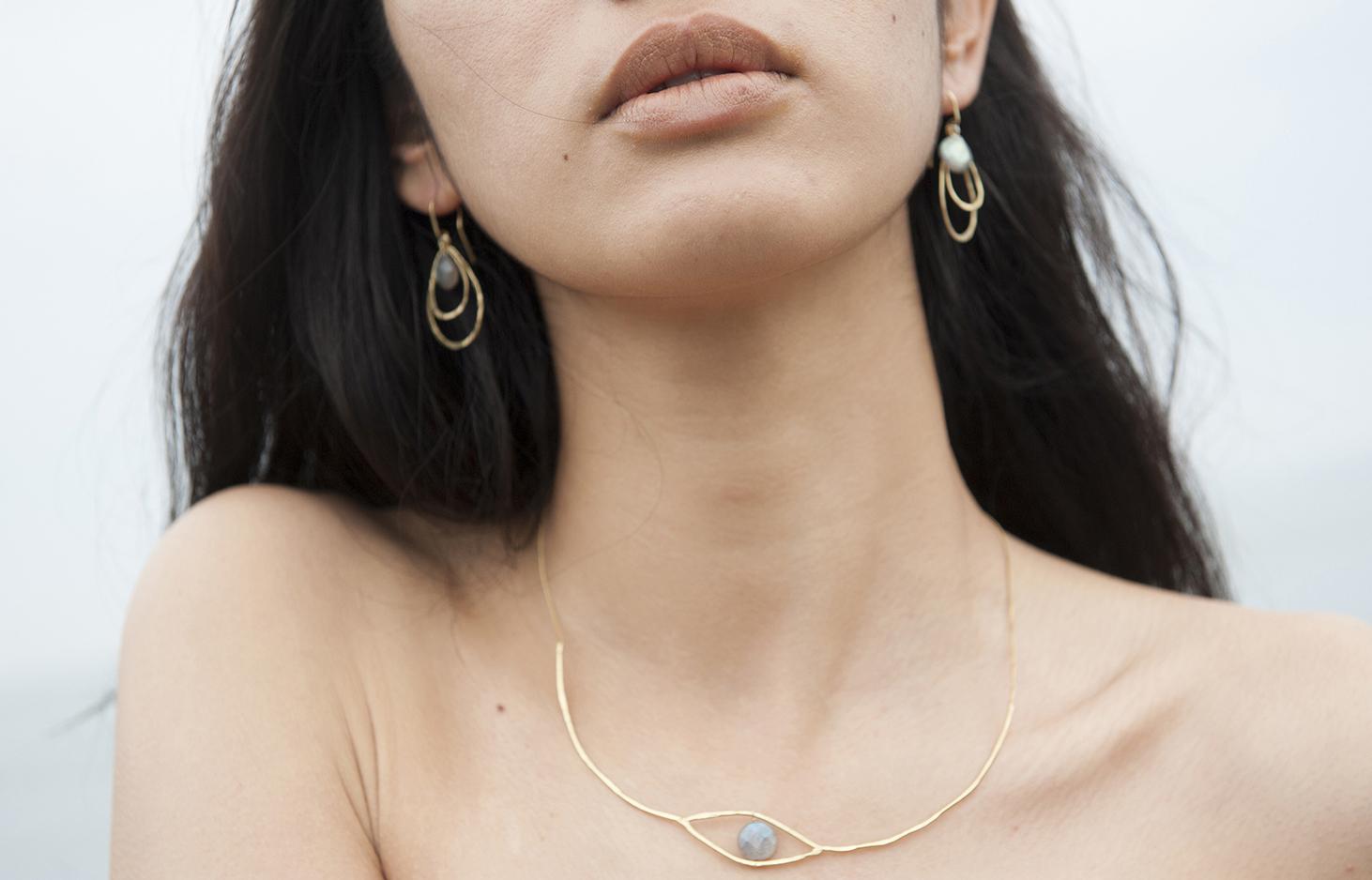 Eri Oya porte un collier rigide, forme de l'oeil, les boucles d'oreilles Pluies, goutte, pierres semi précieuses.