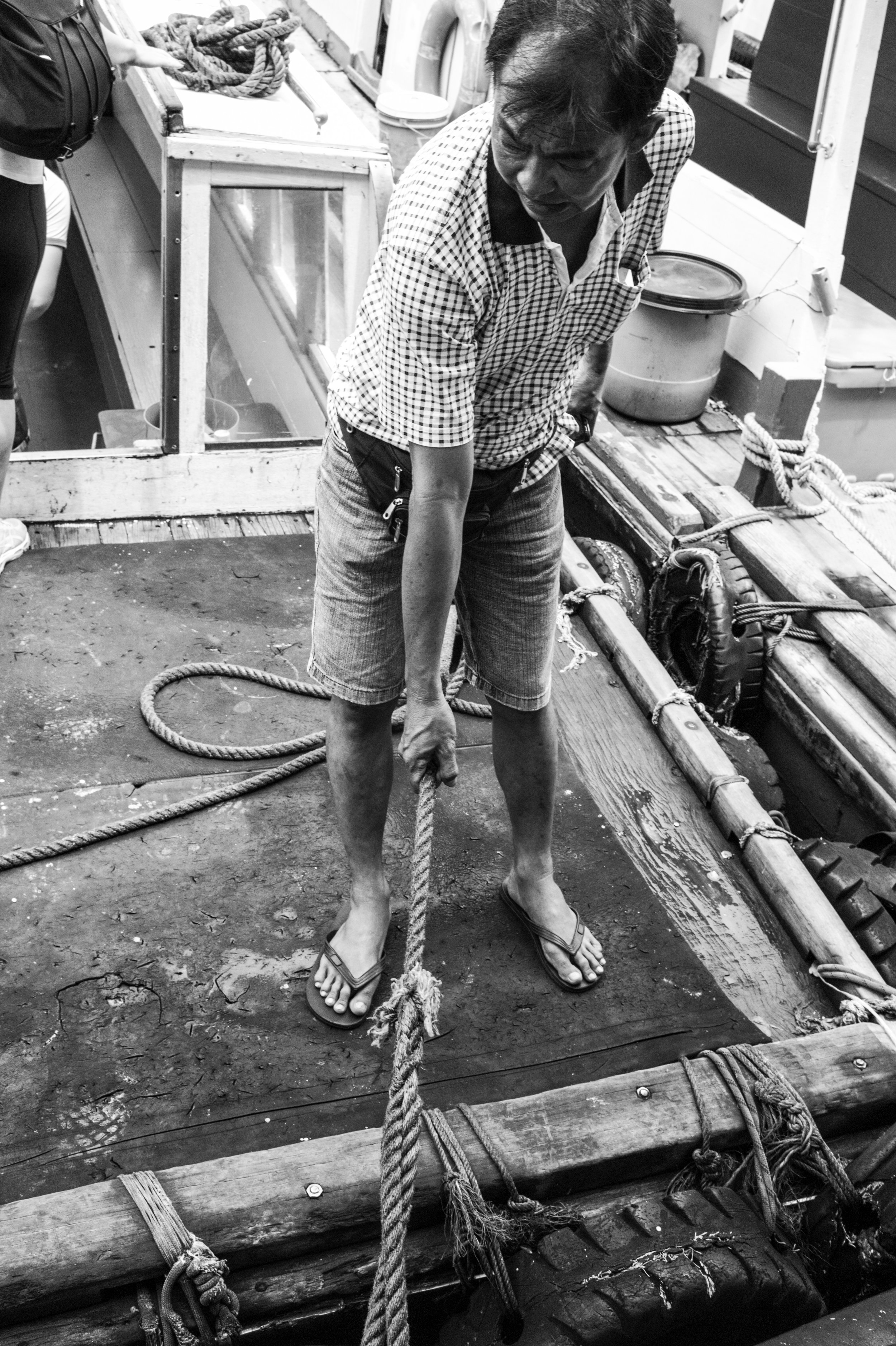 Watch your step . A boatman maintains a bumboat in steady position for passengers to board safely onto the vessel.