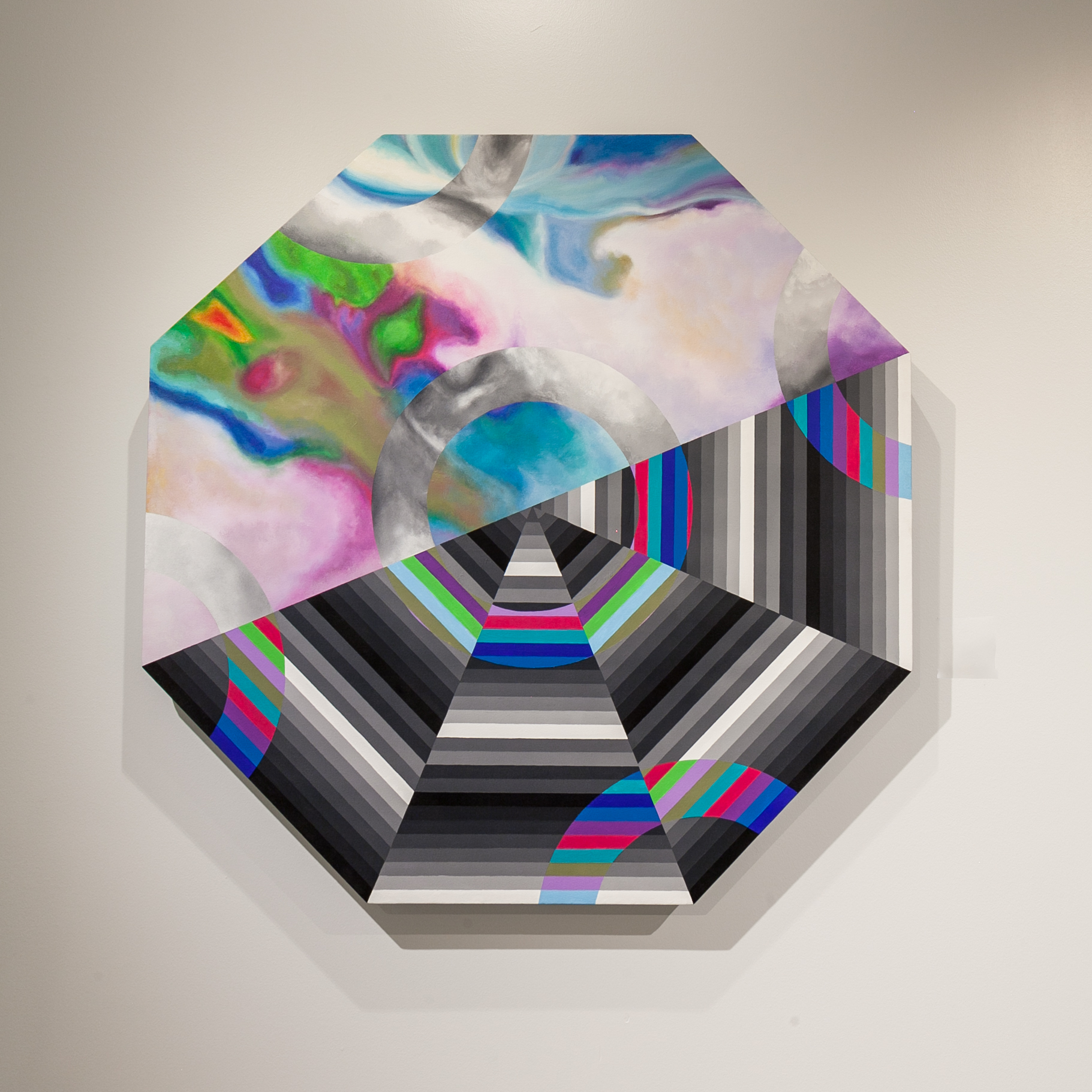 "Paige Ellens (Memphis, TN)   Octagonal Prism , 2019  Medium: Acrylic and ink on canvas  Dimensions: 56x56x3.5 inches  ""In the last year or two, I have become obsessed with line work and using repetitive patterns. I also love experimenting with colors that work to make some sort of optical illusion. In this piece, I worked with a zoomed in photograph of an iridescent bag as a reference for my background. Overlaid, I have line work that mimics the octagonal shape. It can be seen from afar because of its size, yet up close even more can be discovered.""  – Paige Ellens"