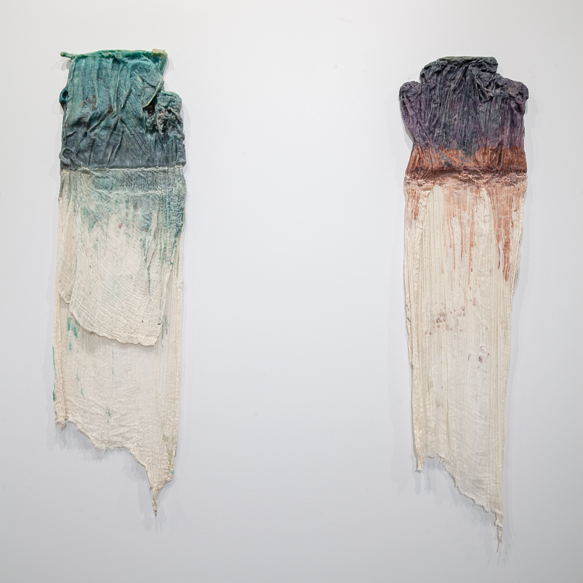 "Lacy Mitcham Veteto (Memphis, TN)   Soft Skeleton  (Diptych), 2018  Medium: Cheesecloth and wax  Dimensions: 63x30 inches each    "" Soft Skeleton  was made through a process of casting and carving wax to expose the internal structure of undulating fabric suspended in the wax. I started using wax because of its flexibility and the way it layers, which I associate with the layering that make up the body.""  – Lacy Mitcham Veteto"
