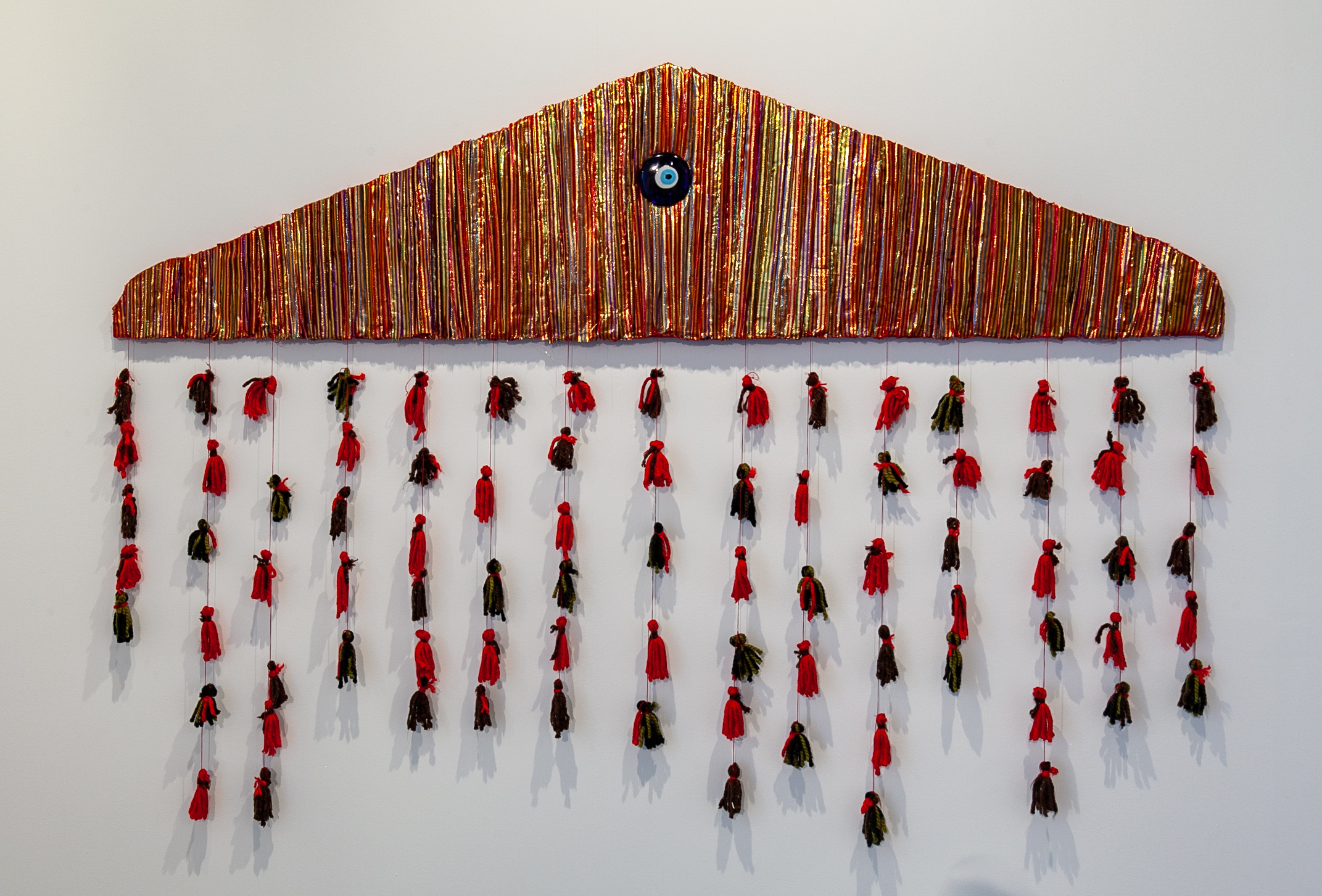 "Nuveen Barwari (Nashville, TN)   House Wife , 2018  Medium: Fabric, acrylic paint, glass, and yarn on wood  Dimensions: 58x83 inches  ""This piece was inspired by the Kurdish women presiding in my life. For years, I have watched members of my family create traditional pieces with fabrics such as Kurdish dresses and tassels attached to tapestries inside of houses. Through this piece my aim was to protect and honor their craft, ideology and identity. In most Kurdish homes you will find an 'evil eye' as a symbol of protection."" – Nuveen Barwari"
