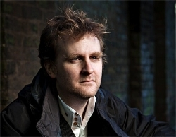 Nick Harkaway is the author of  Gnomon , as well as  The Gone-Away World ,  Angelmaker  (for which he won the Oxfam Emerging Writers Prize and the Kitschies' coveted Red Tentacle) and  Tigerman .   He has been described variously as 'J. G. Ballard's geeky younger brother', 'William Makepeace Thackerary on acid' and 'a British mimetic speculative godgame novelist'.   The Blind Giant , his only full length non-fiction work, examined the interaction of technology and humanity and how best to live in a world where gadgets have become fundamental.   @harkaway   Nick's photo taken by Rory Lindsay