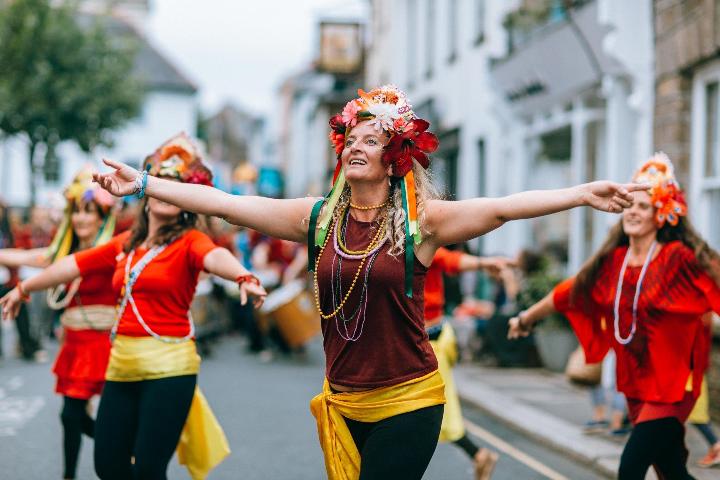 A group of dancers lead the Penryn Kemeneth procession down Penryn high street. Penryn, Cornwall, UK. 14th Oct 2017.