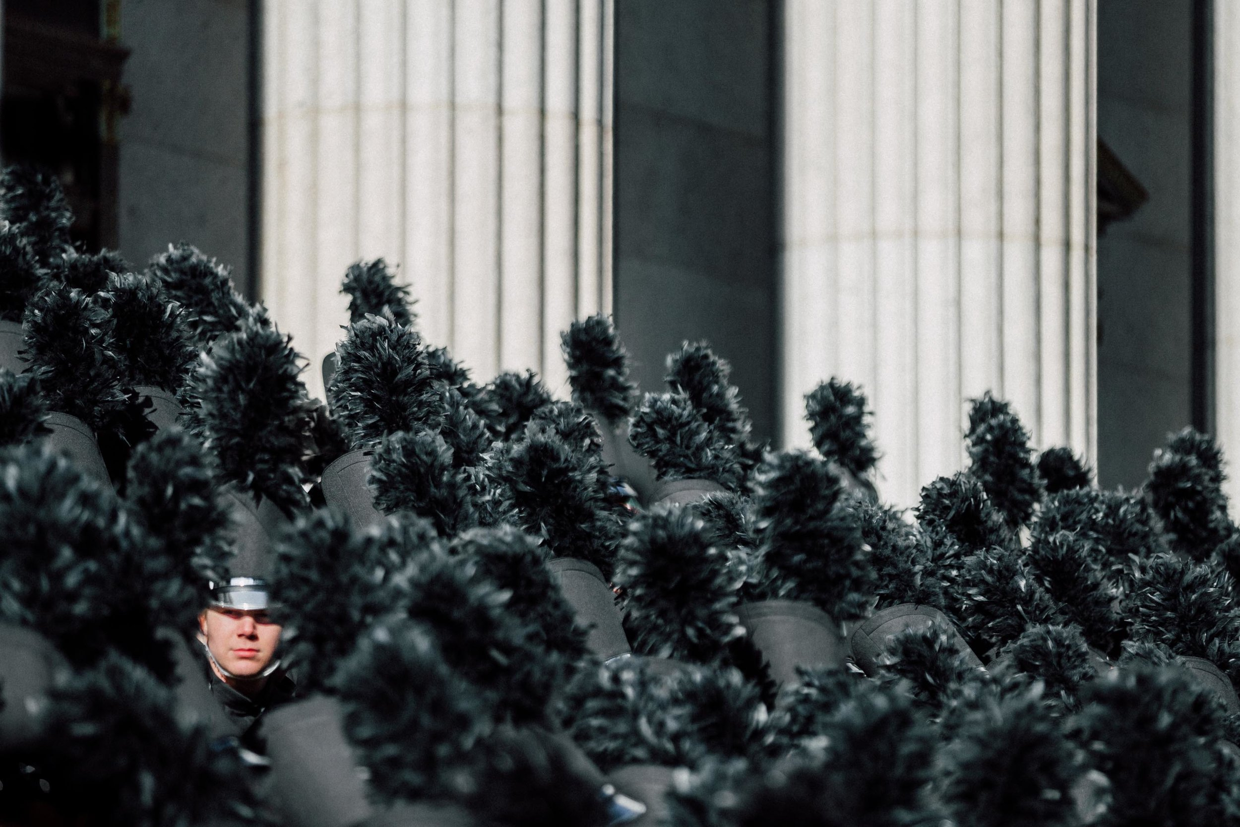 A face looks through a crowd of feathered hats belonging to a marching band in the Macy's Thanksgiving Day Parade, as they stand outside the James A. Farley Post Office Building, New York. 23rd Nov 2017.